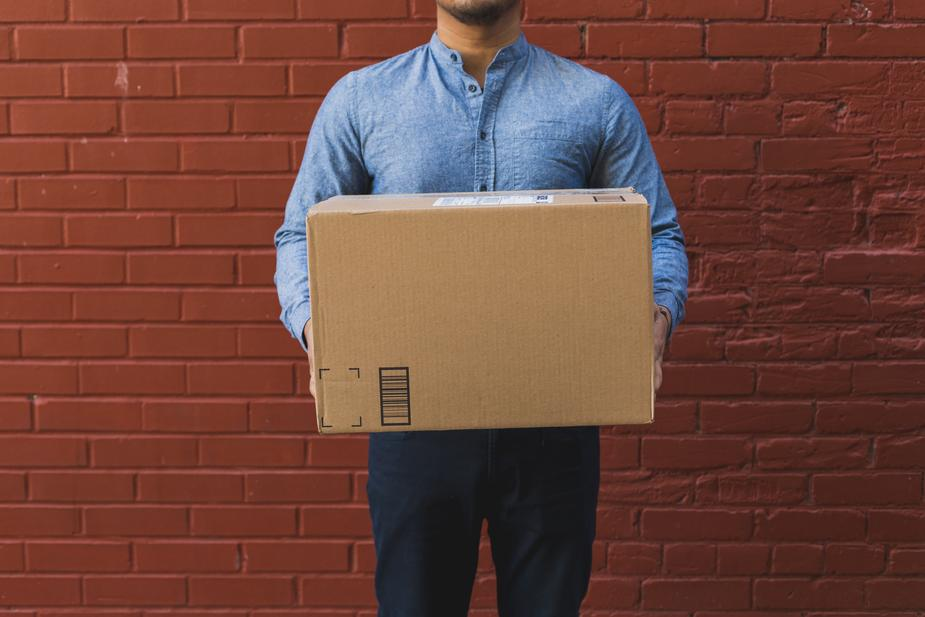 man-holding-shipping-box-on-red-brick_925x.jpg