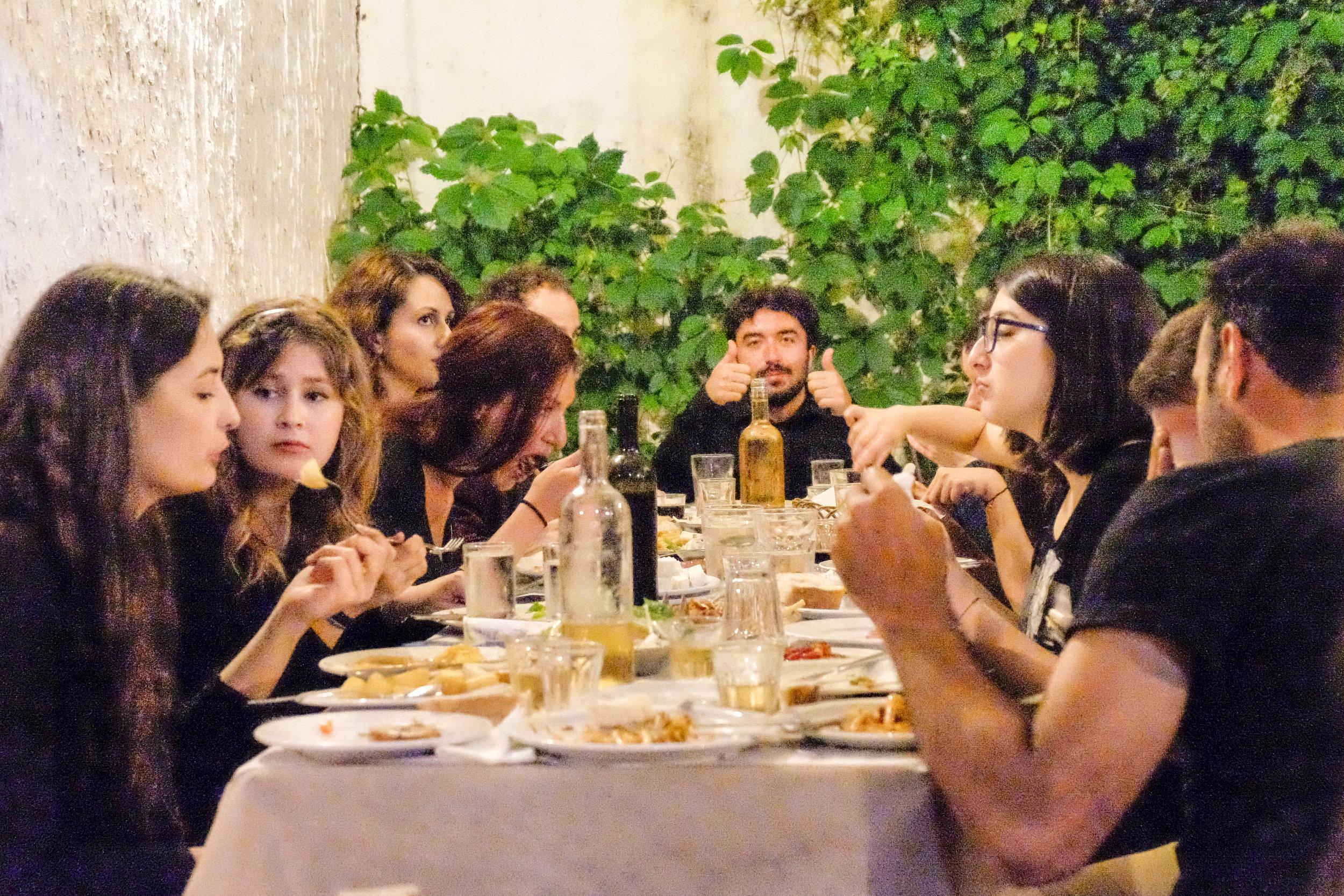 A group of friends enjoys dinner in taverna trips garden patio