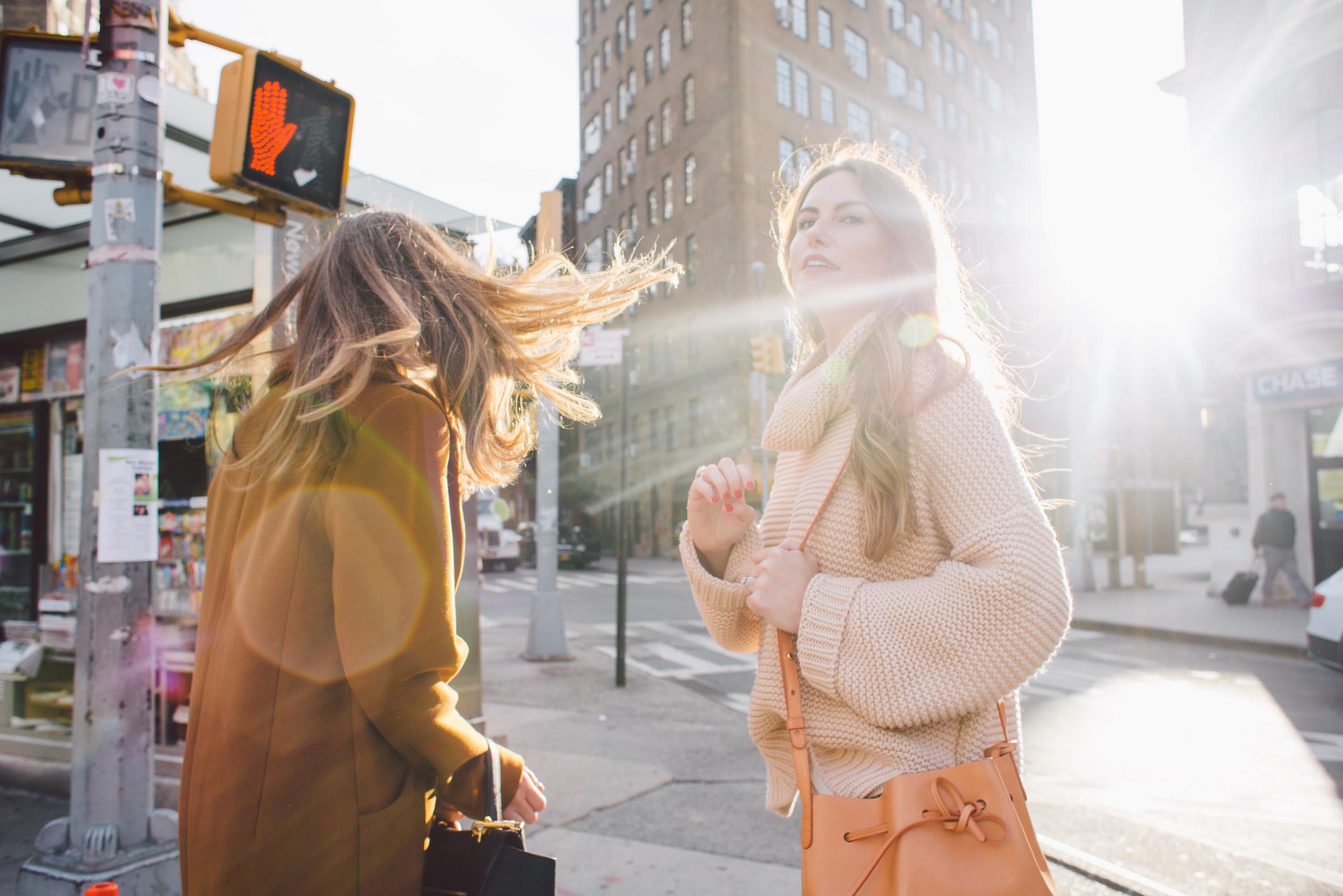 a pair of women wait at a new york city crosswalk. (credit: moyo oyelola)