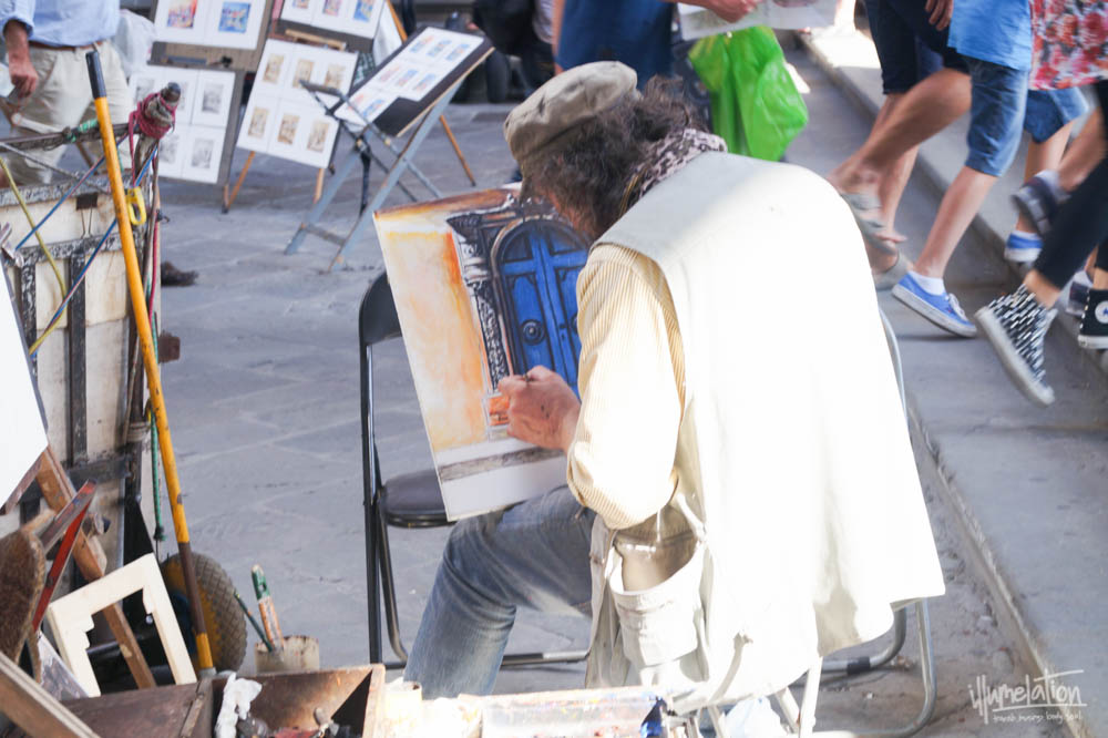 Street artist in Florence, Rome. Man hunched over his easel painting a door. illumelation.