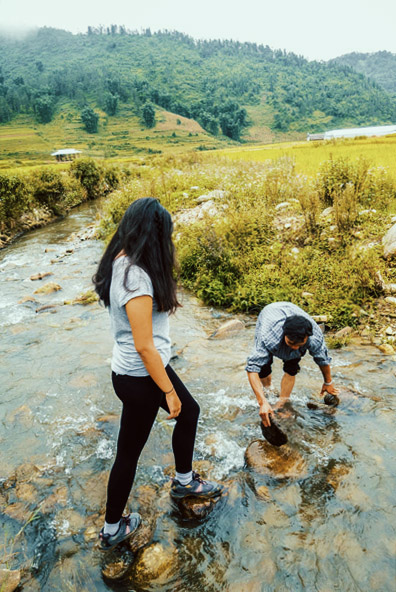 Lua (May Kieu) puts down rocks in Sapa Vietnam.