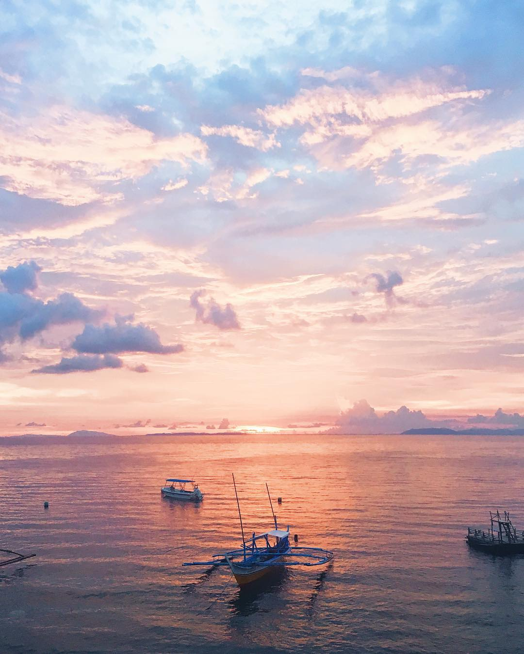 Pink sunset with purple clouds and fishing boats floating on still water in the Philippines