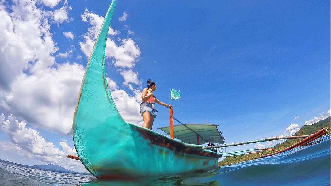 Girl standing on a blue boat on the water with clouds and blue sky by Taal Volcano