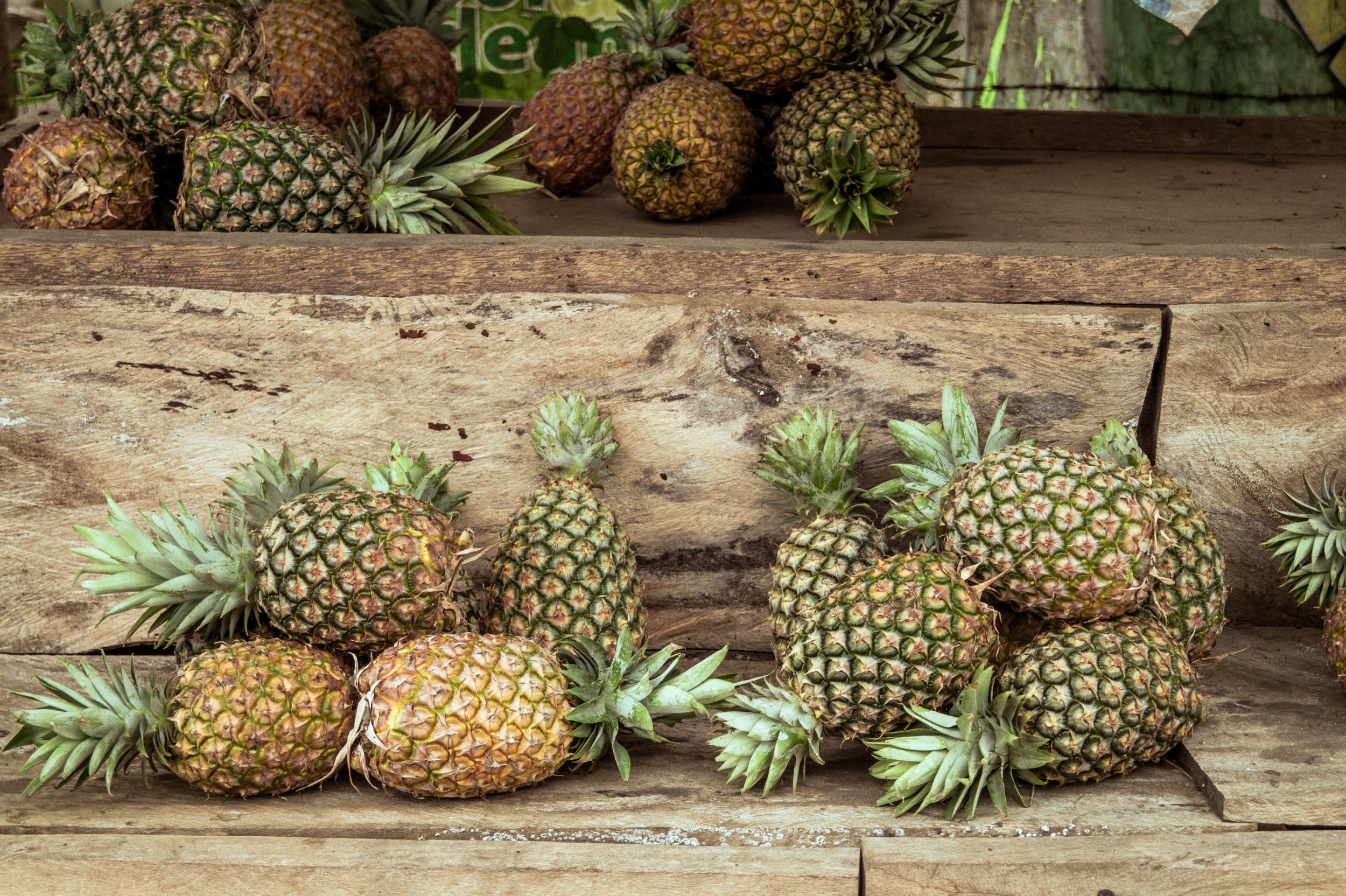 Small Philippine pineapples on a rustic wooden bench