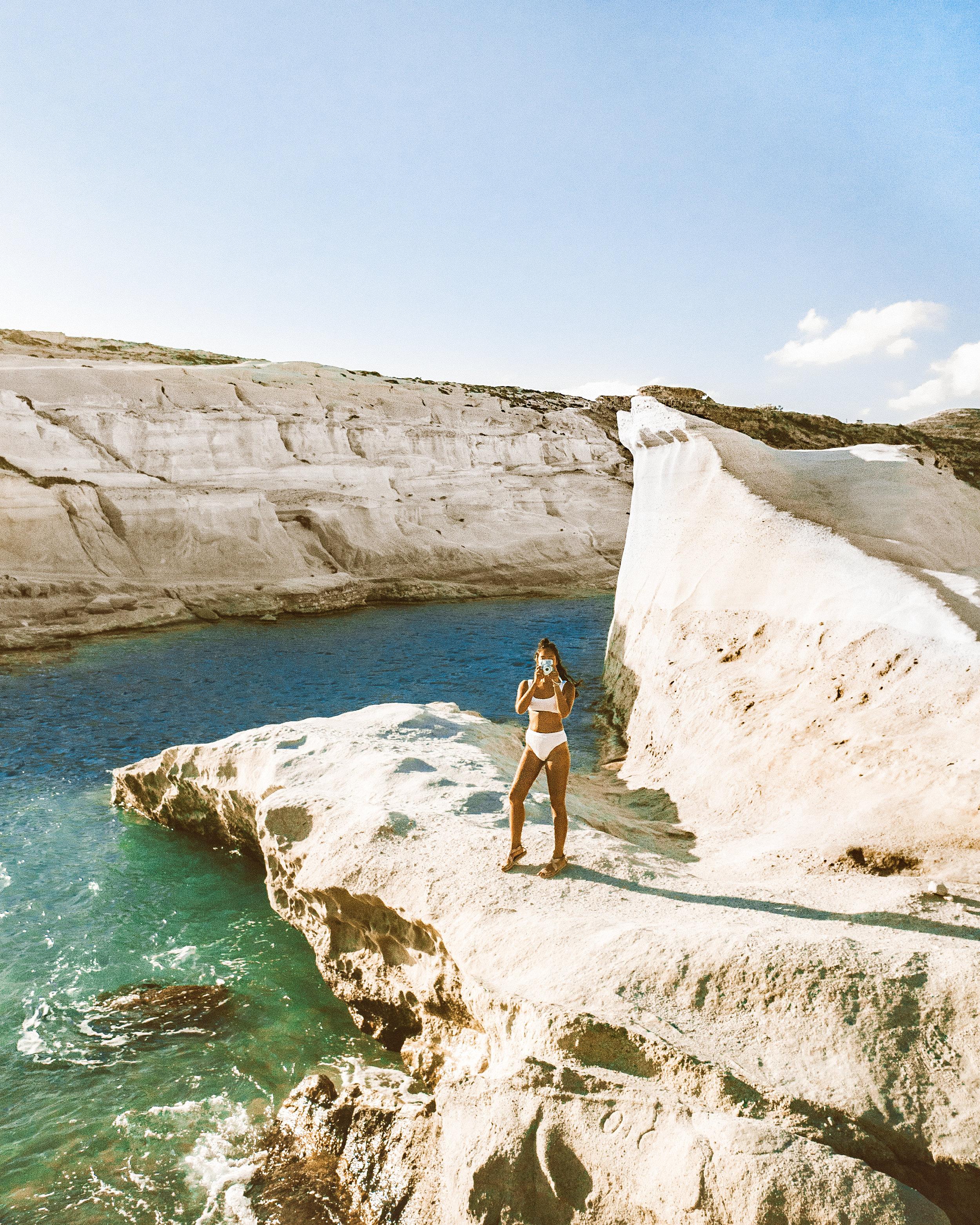 Mel in a white bikini standing on Sarakiniko Beach in Milos, Greece, taking a Polaroid photo at sunrise