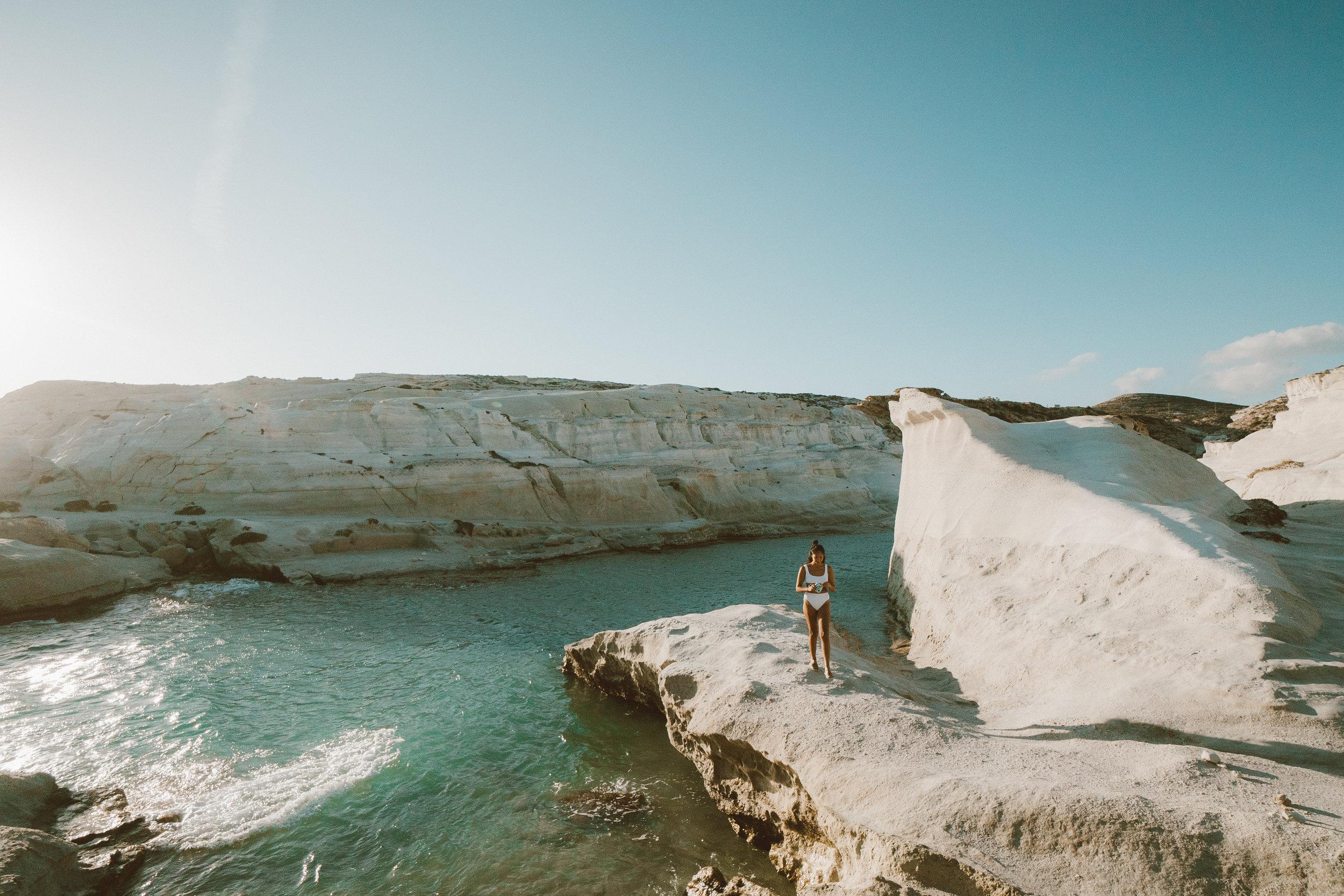 Mel in a white bikini standing by the sea on Sarakiniko Beach in Milos, Greece, holding a polaroid camera