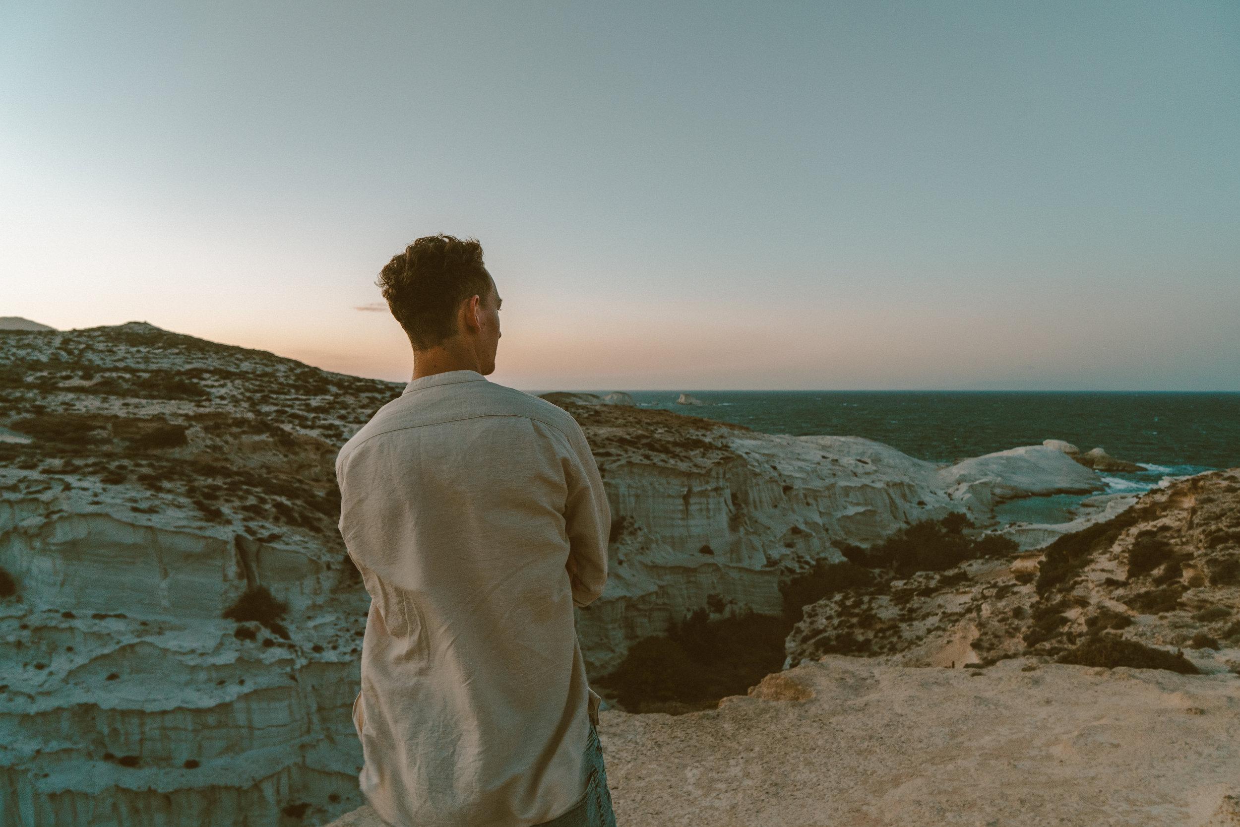 Harry man standing facing the ocean on Sarakiniko Beach in Milos, Greece, at sunset