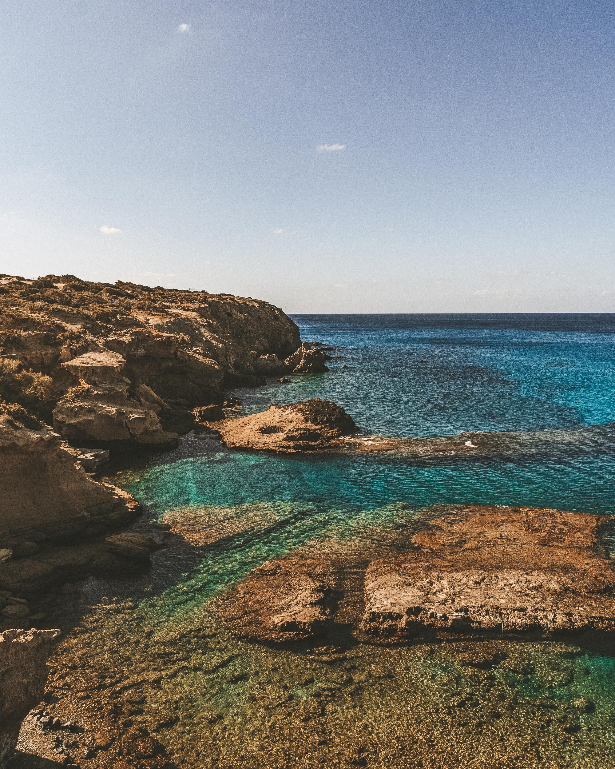 希腊米洛斯的普拉蒂耶诺海滩,令人惊叹的蓝色大海和崎岖的棕色岩石