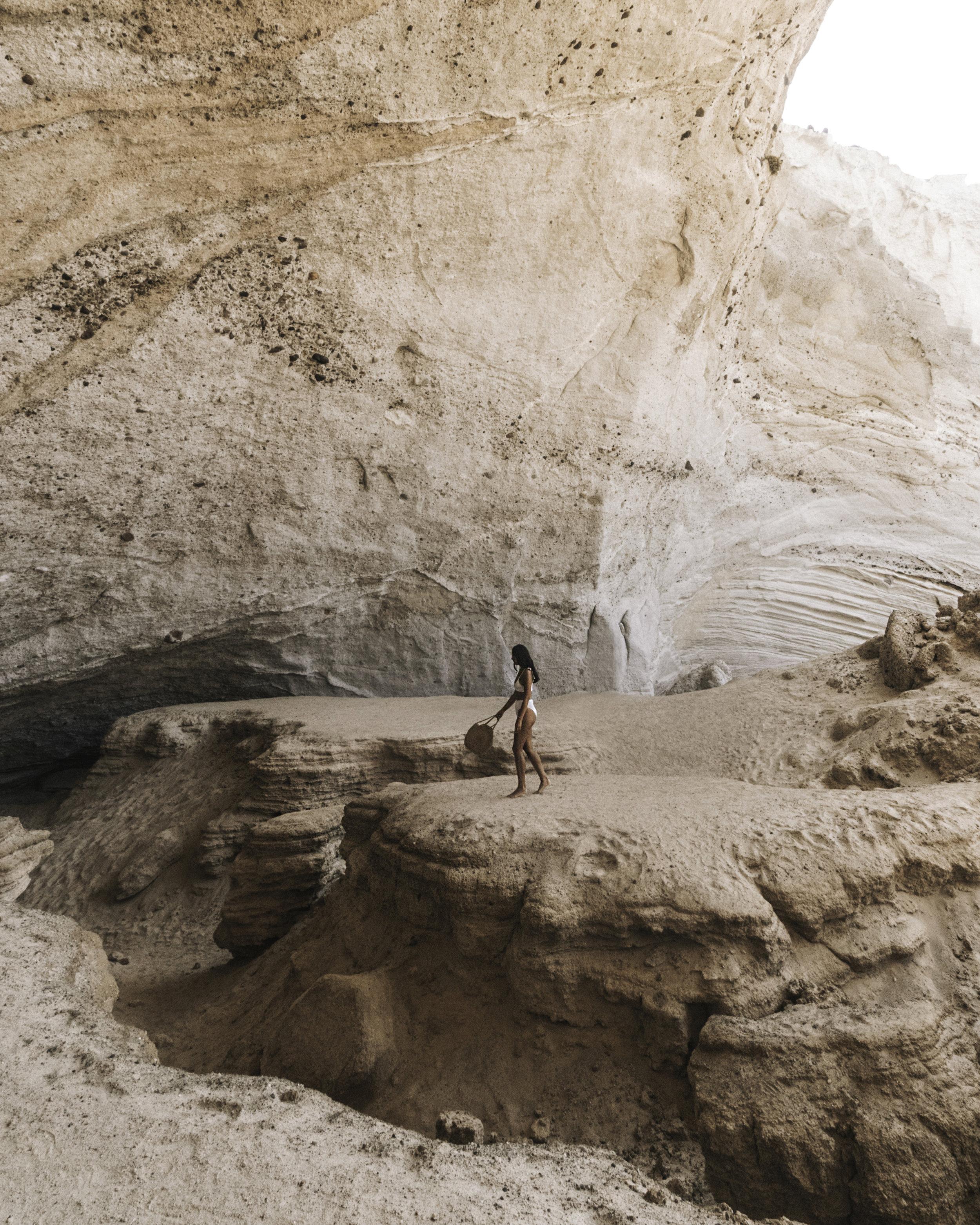 梅尔穿着白色比基尼,挥舞着一个草包,探索希腊米洛斯的锡基亚海洞