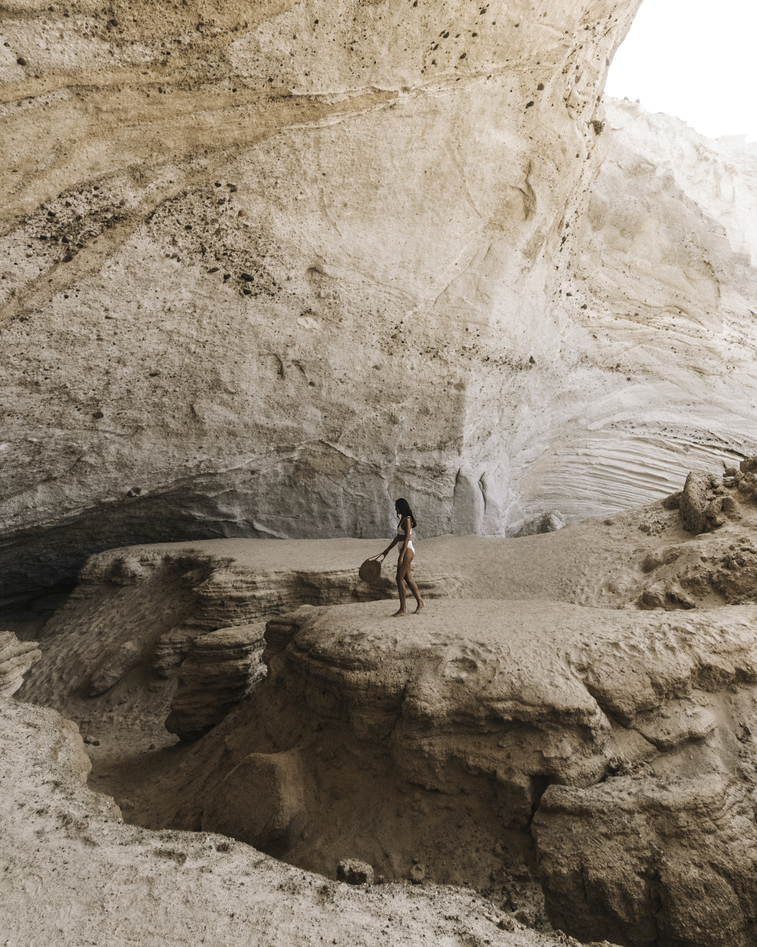 Mel wearing a white bikini swinging a straw handbag exploring Sykia Sea Cave Milos Greece
