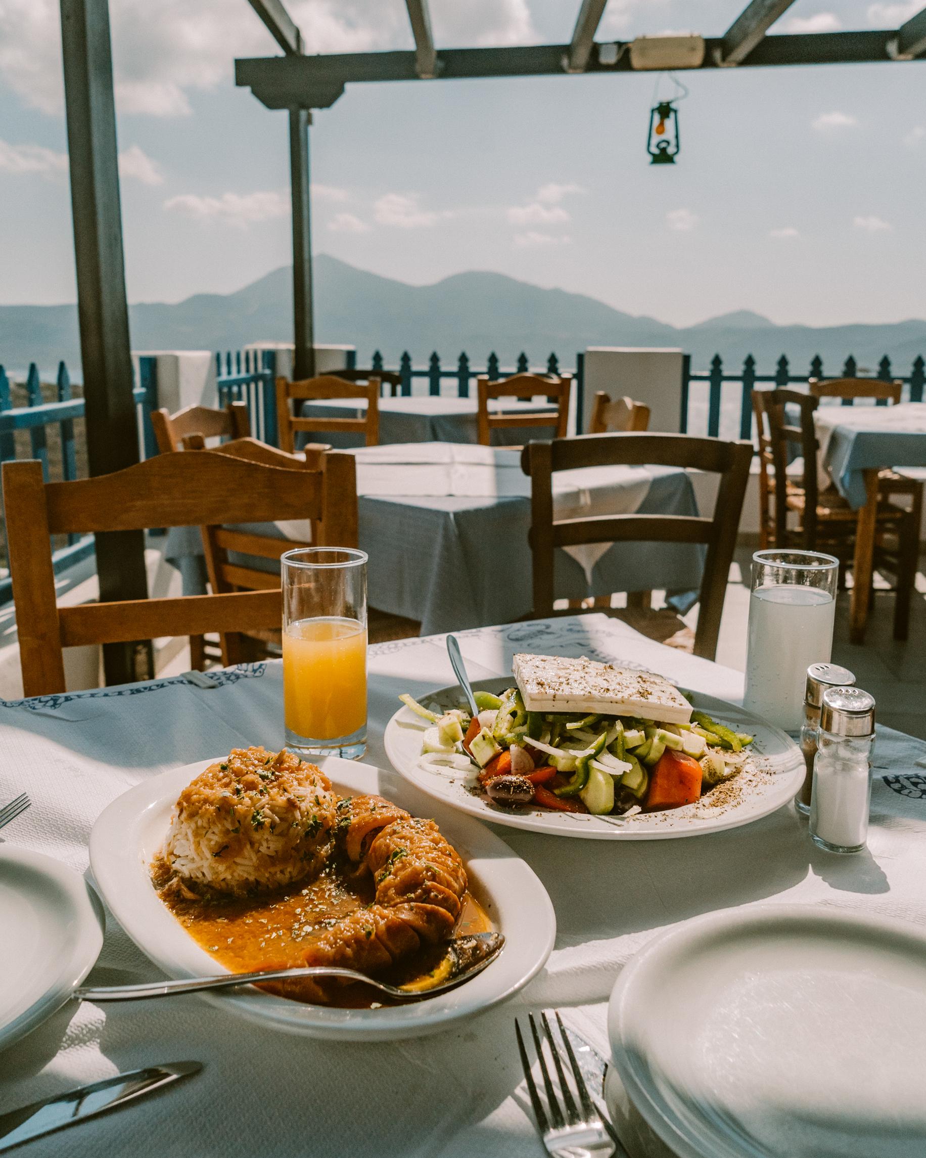 希腊米洛斯市普拉卡的Ergina酒馆的新鲜希腊沙拉和鱿鱼特色菜