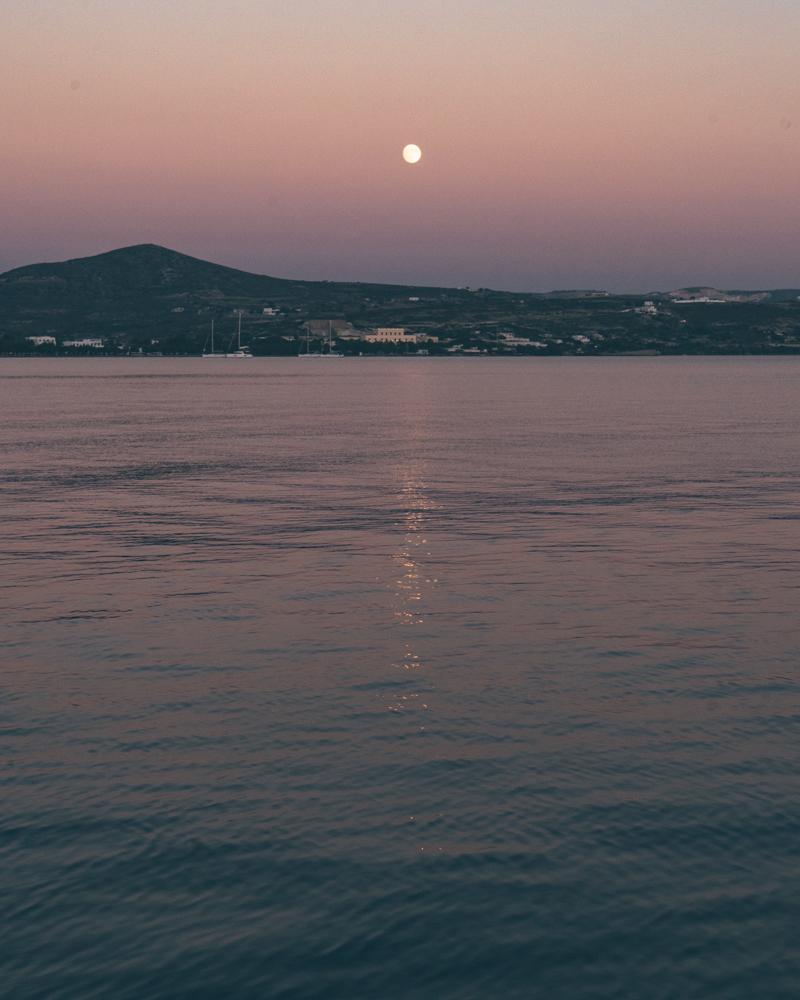 Moon rising over the sea in Milos, Greece