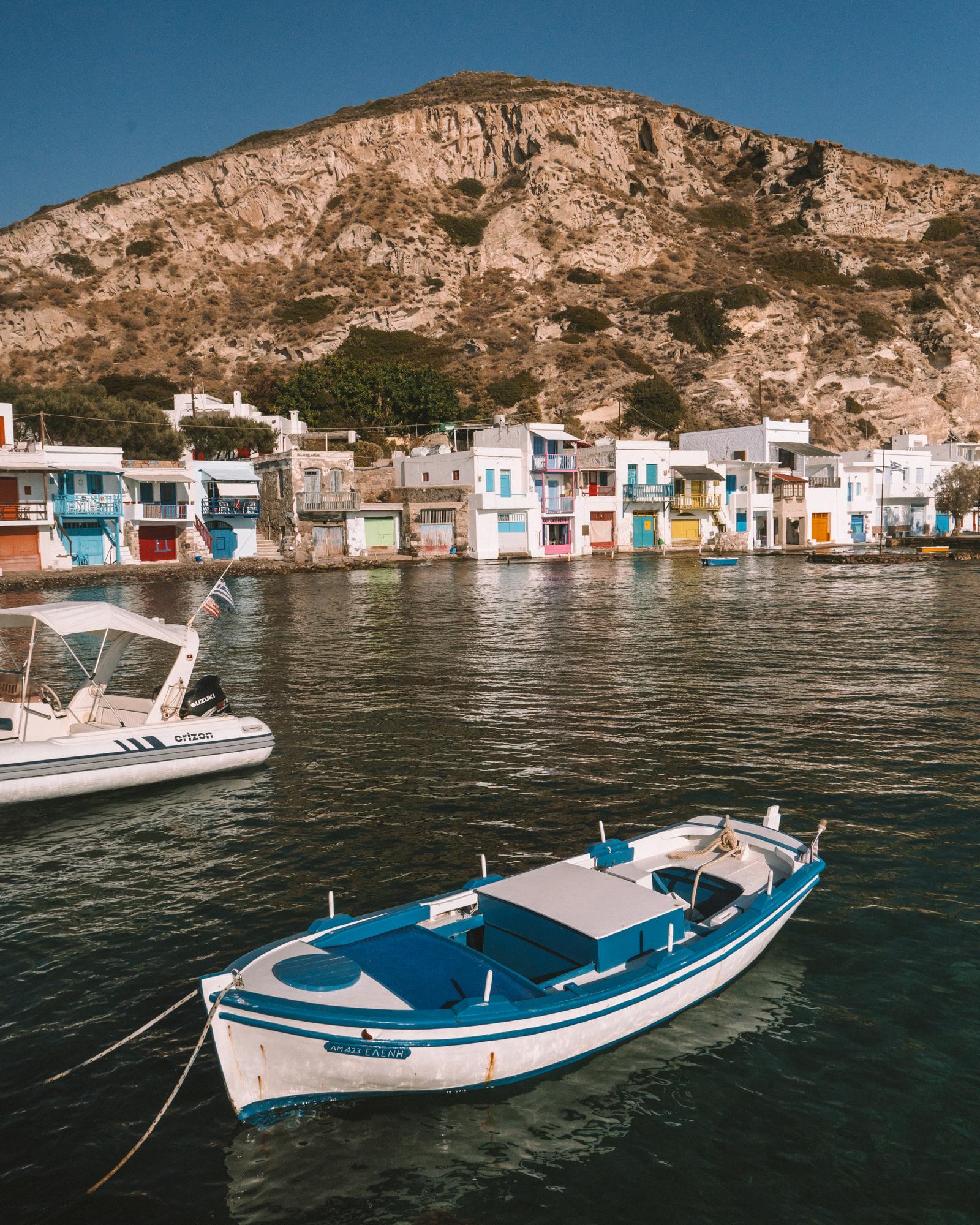 希腊米洛斯的Klima渔村,一艘蓝白相间的渔船漂浮在海面上