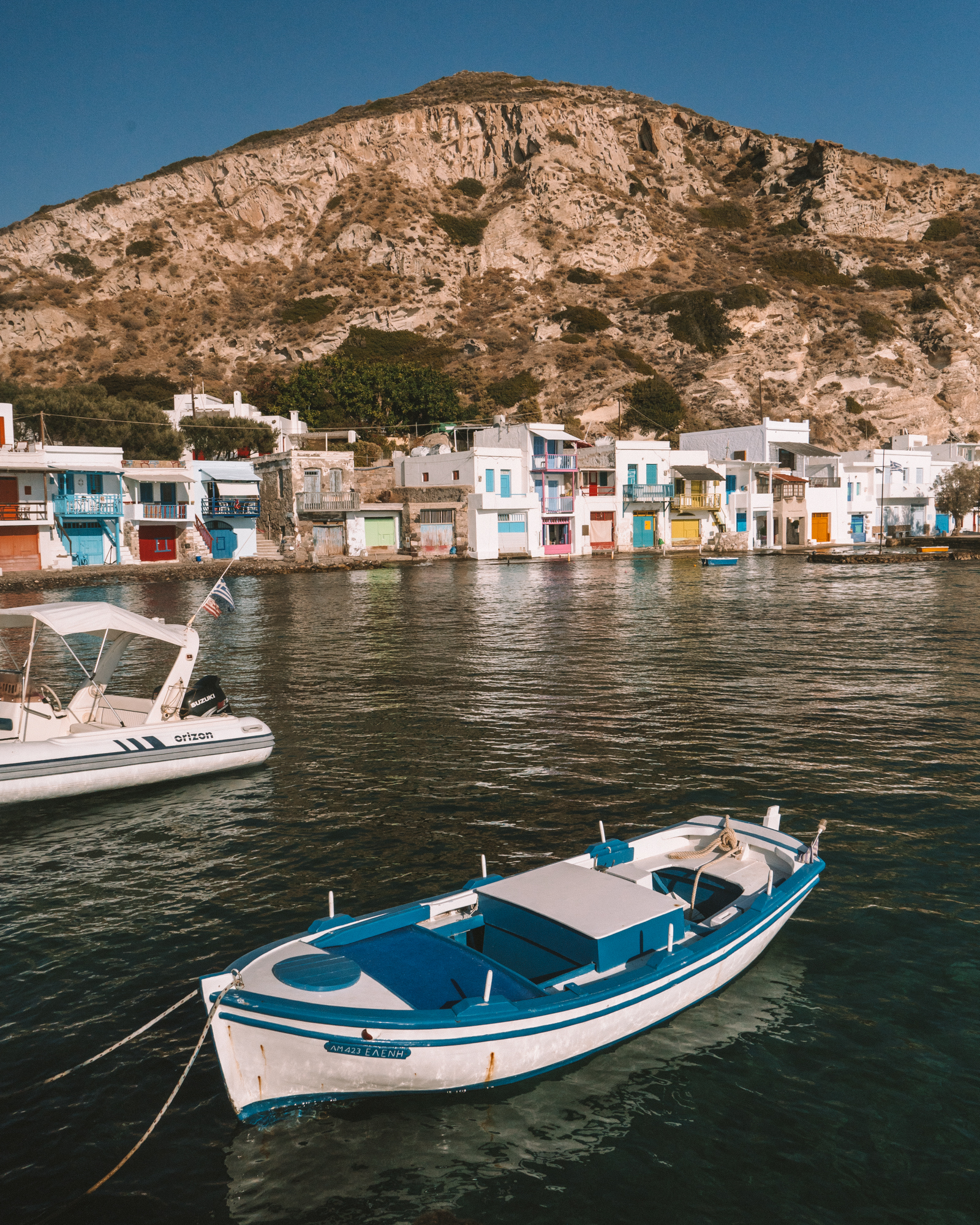 Blue and white fishing boat floating on the sea in Klima Fishing Village in Milos Greece