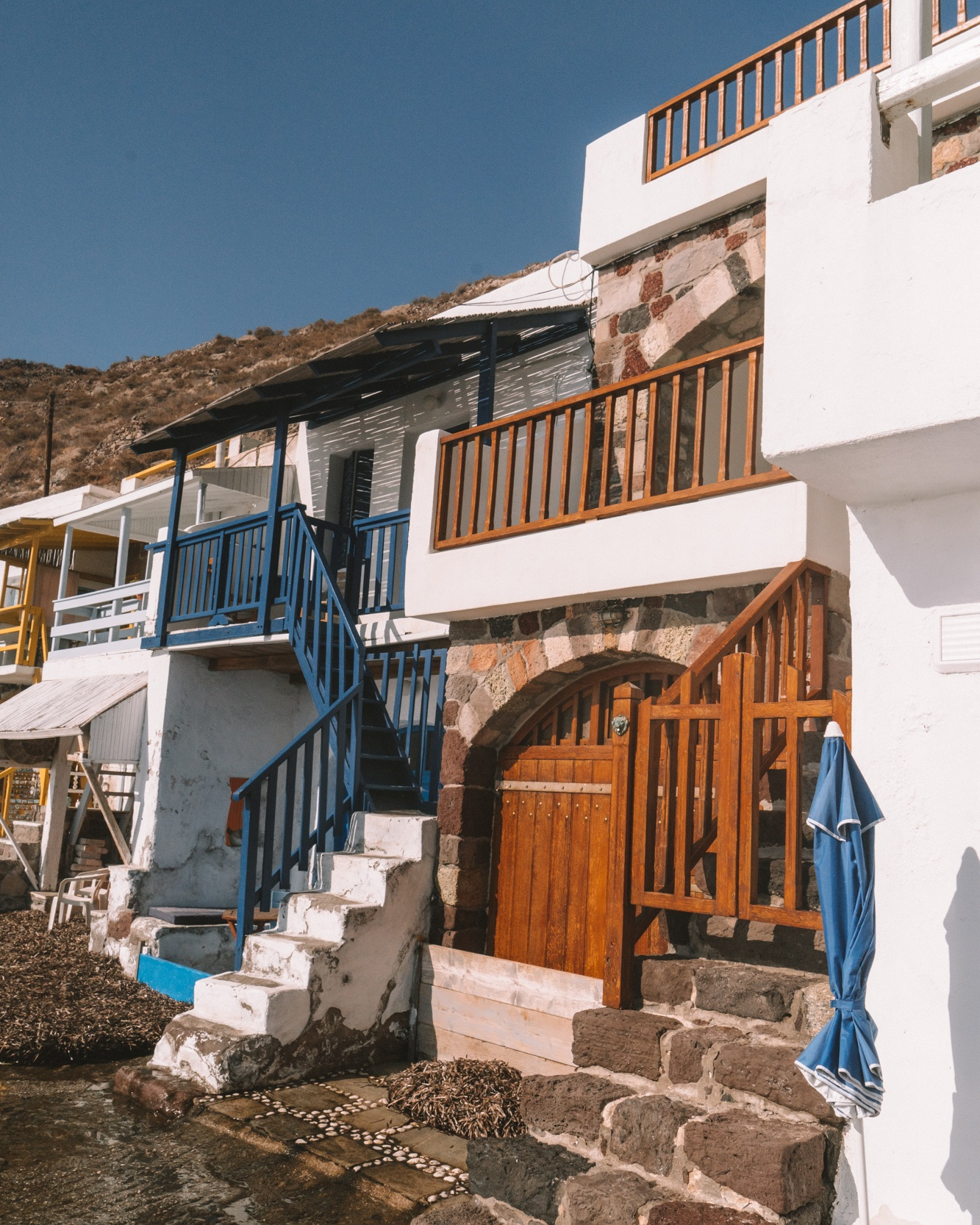 Colourful railings and stone steps of houses in Klima Fishing Village, Milos