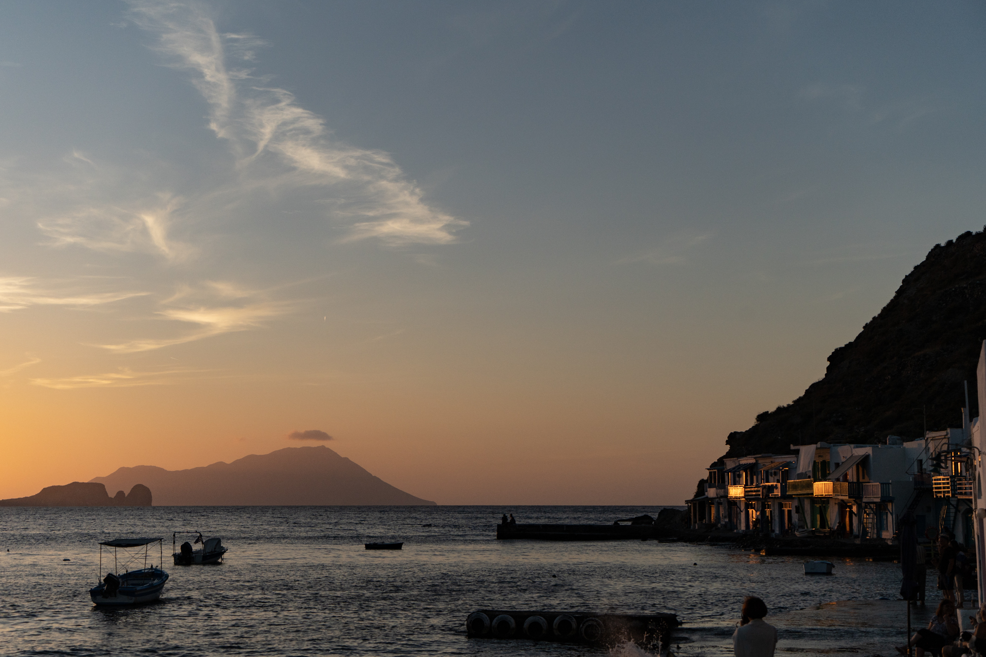 希腊米洛斯的克里马渔村,日落在海面上,地平线上有一座山的轮廓