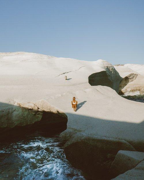 梅尔女孩坐在希腊米洛斯的Sarakiniko海滩上,在光滑的白色石灰石上,一半投在阴影中,海水在下面打转