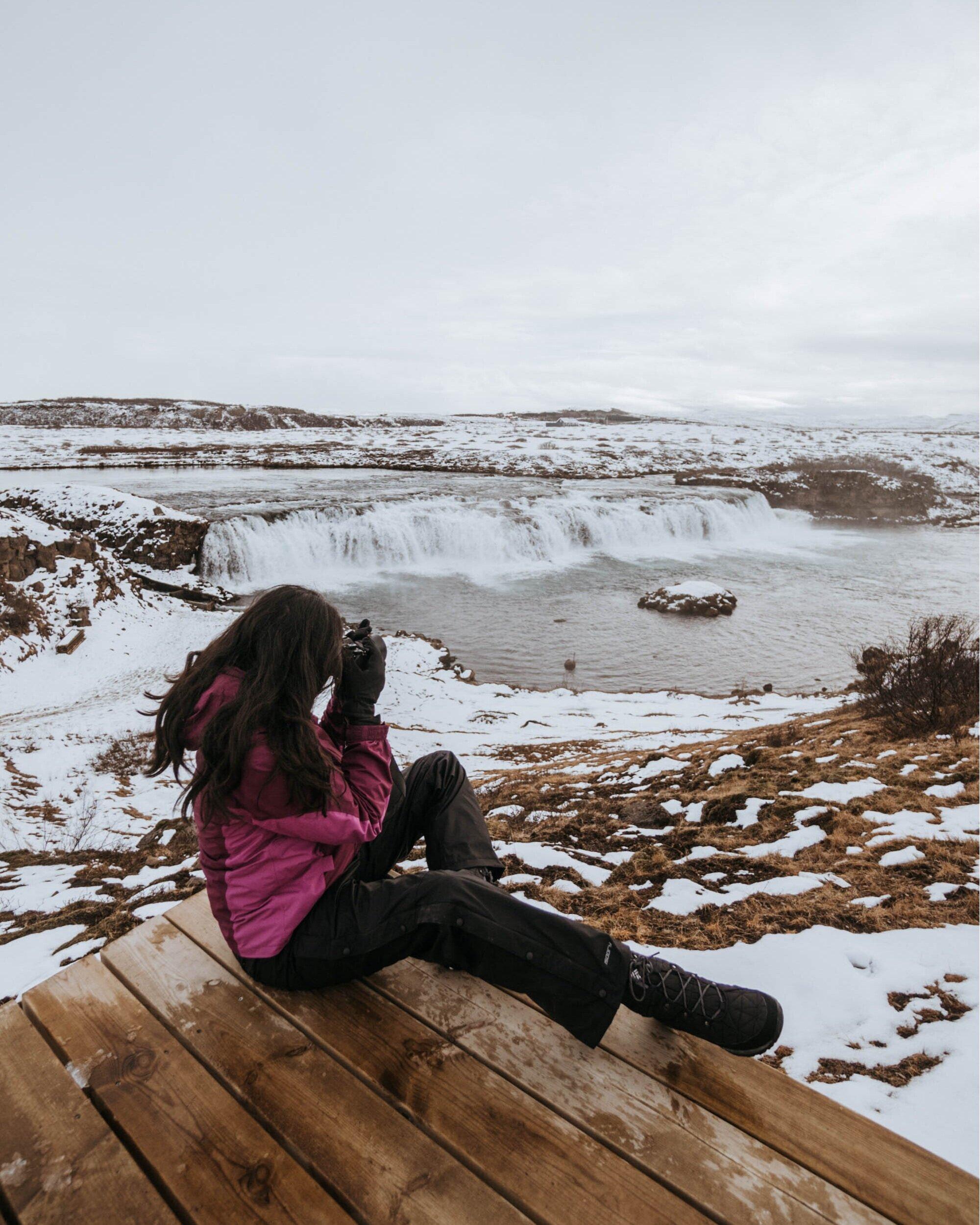 冰岛雪景中坐在木制平台上拍摄格尔福斯瀑布的女孩