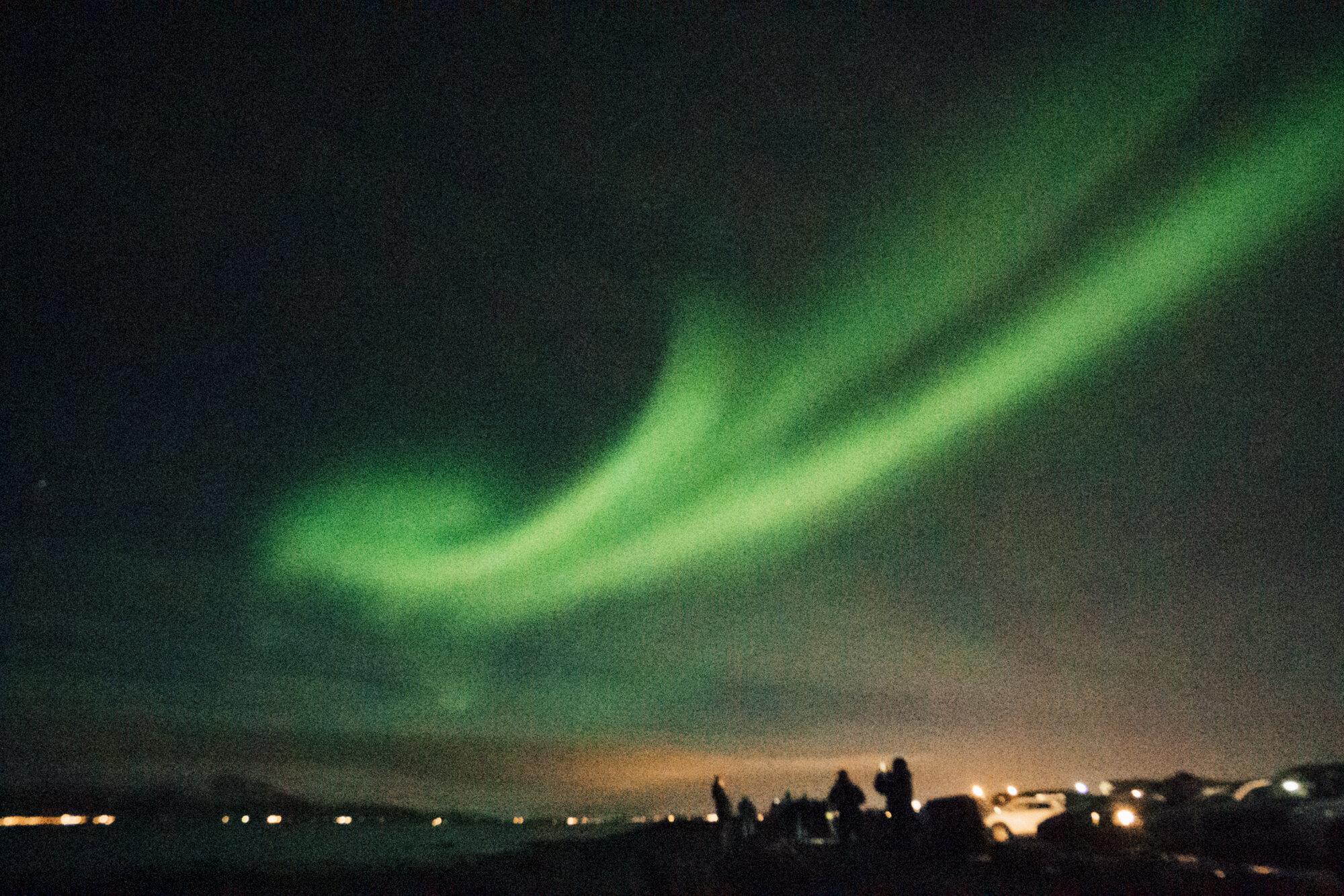 Aurora Borealis的明亮的绿色漩涡在夜空的在雷克雅未克,冰岛