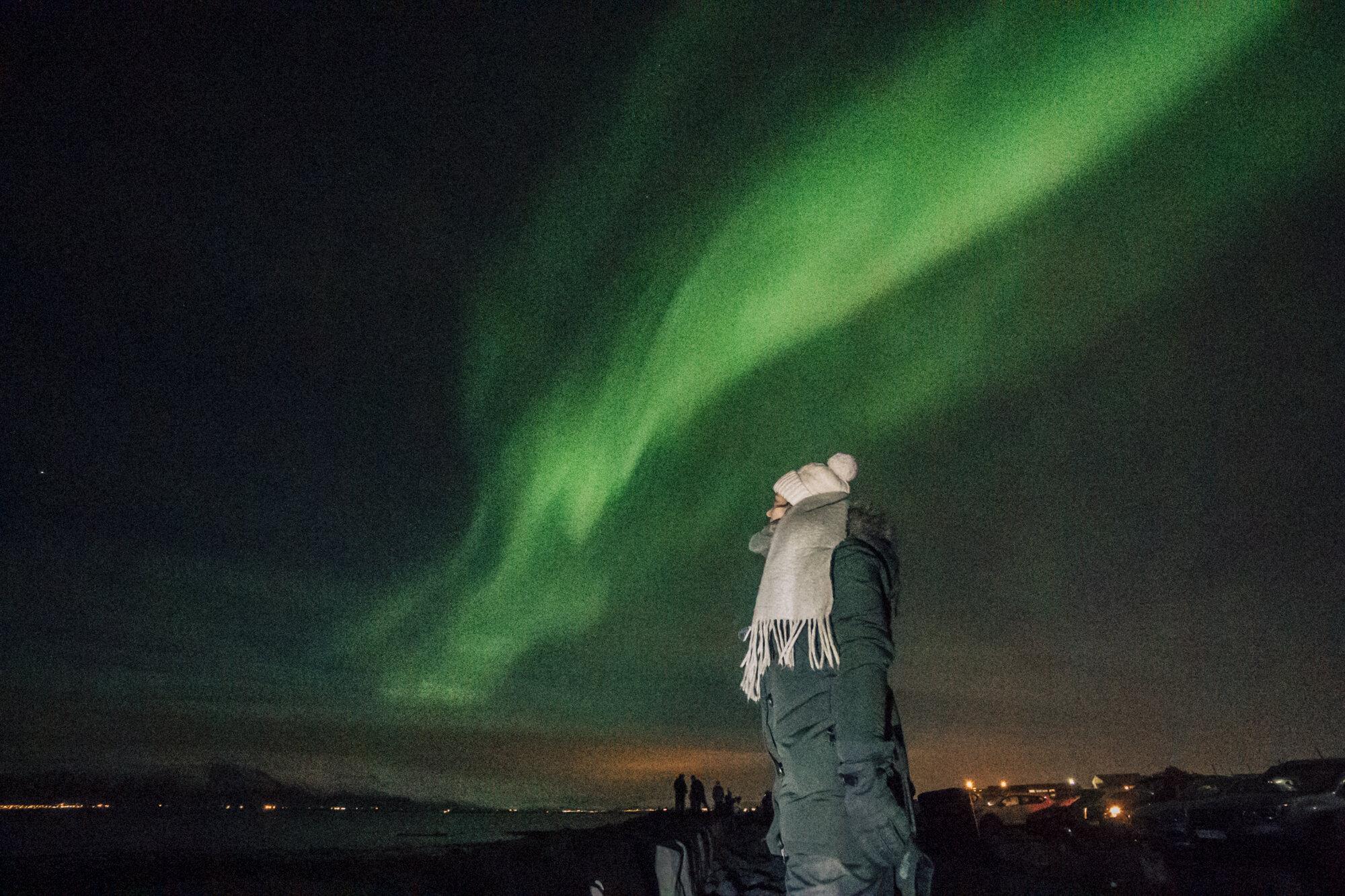 冰岛雷克雅未克,穿着冬衣的女孩站在明亮的绿色北极光下