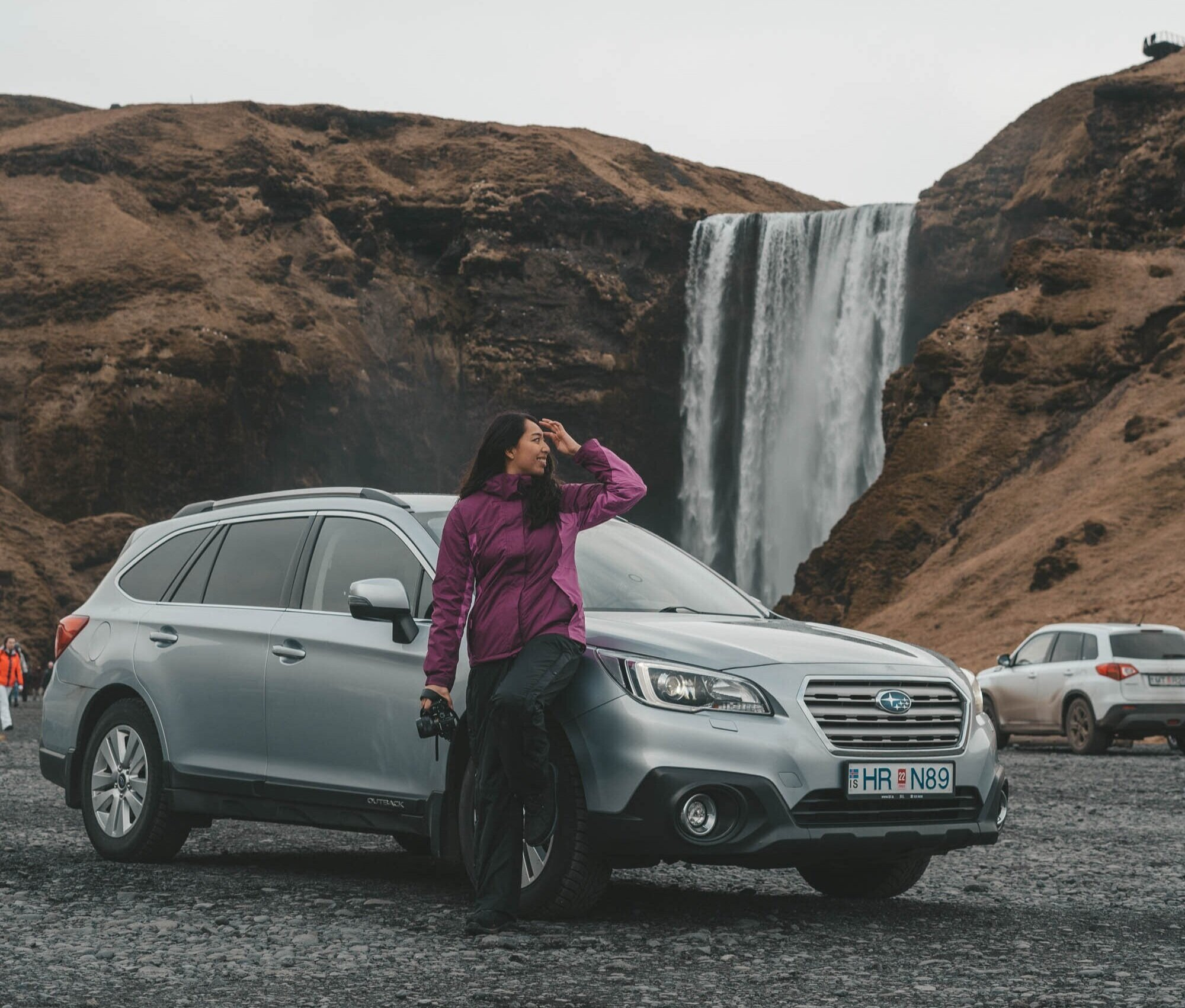 倾斜在汽车的女孩在Skogafoss瀑布外面的冰岛,Subaru内部储蓄