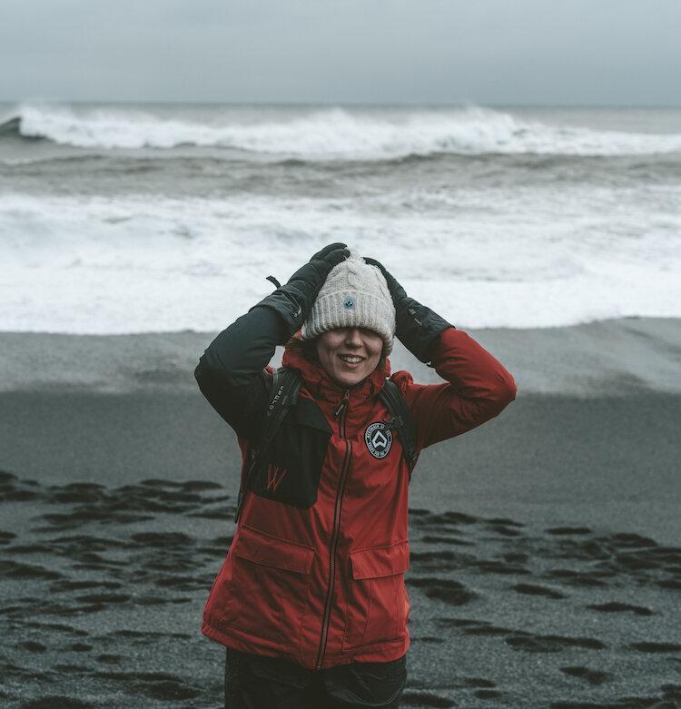在有风的黑色海滩上,穿着红色夹克的女孩手持帽子,背景是波浪