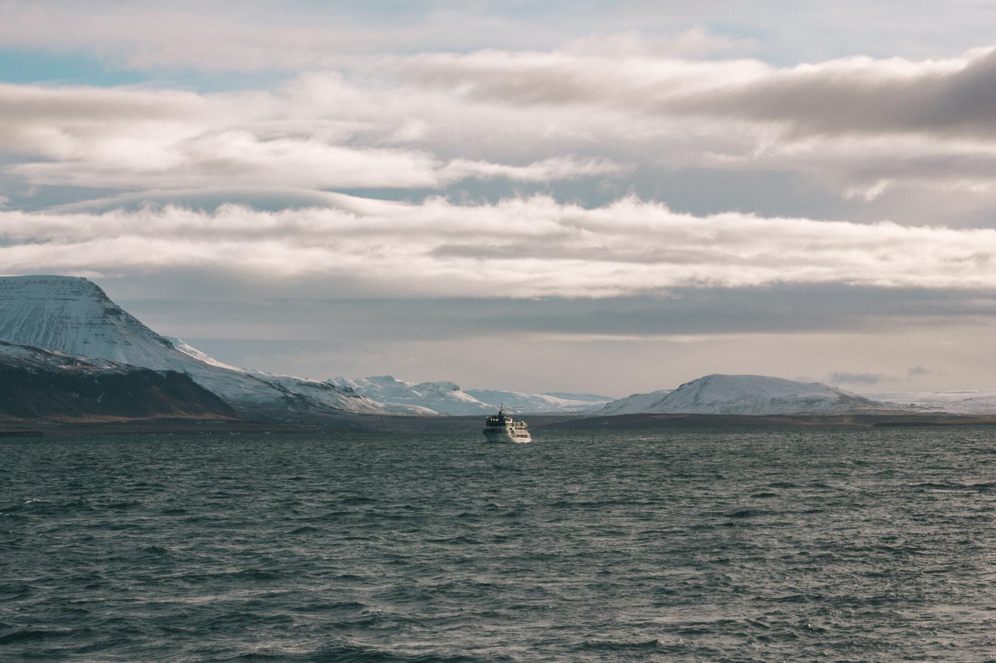 船在格陵兰岛海洋中央,雪山和天空中引人注目的云
