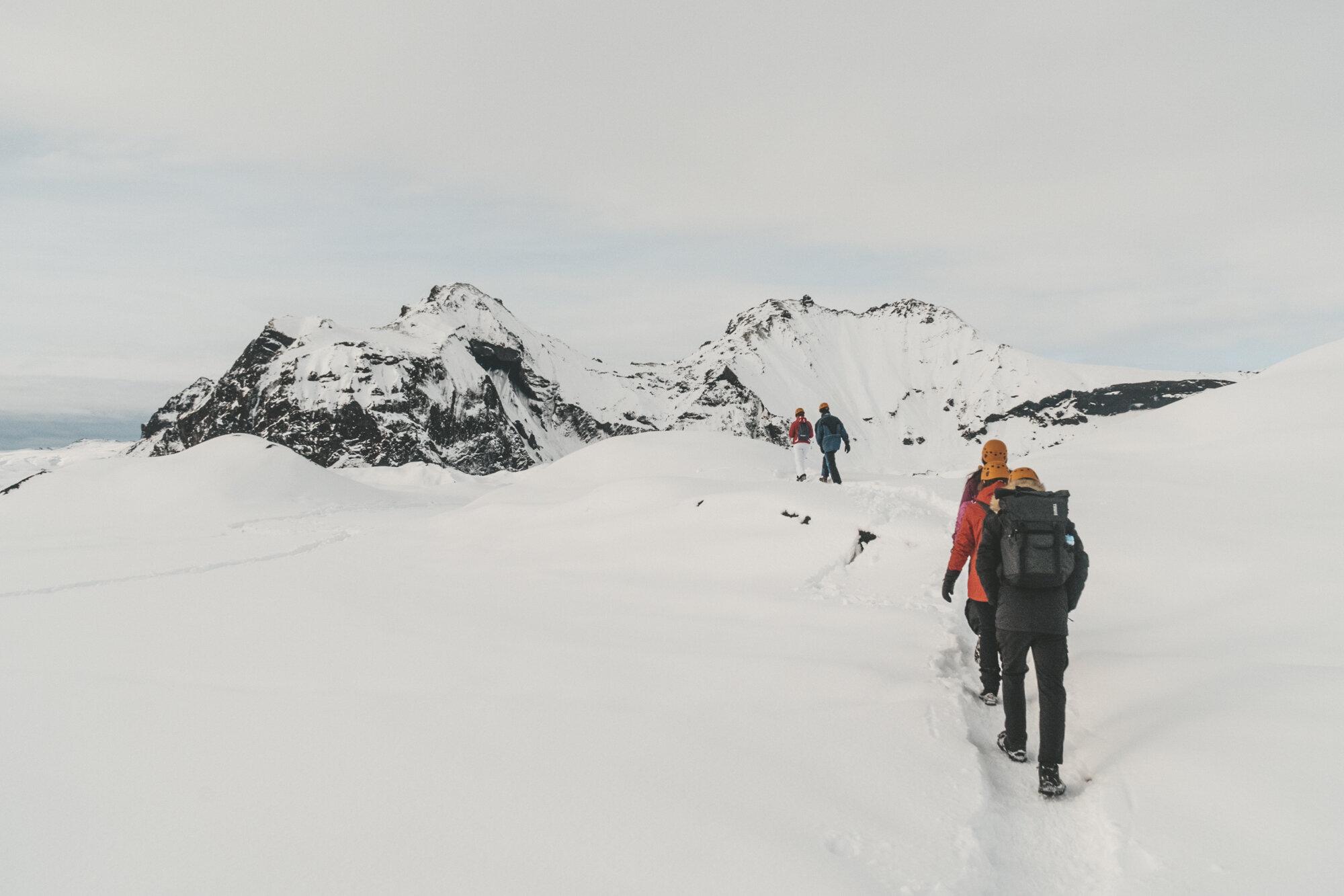 人们穿着冬装,在雪地里向冰岛的黑山跋涉