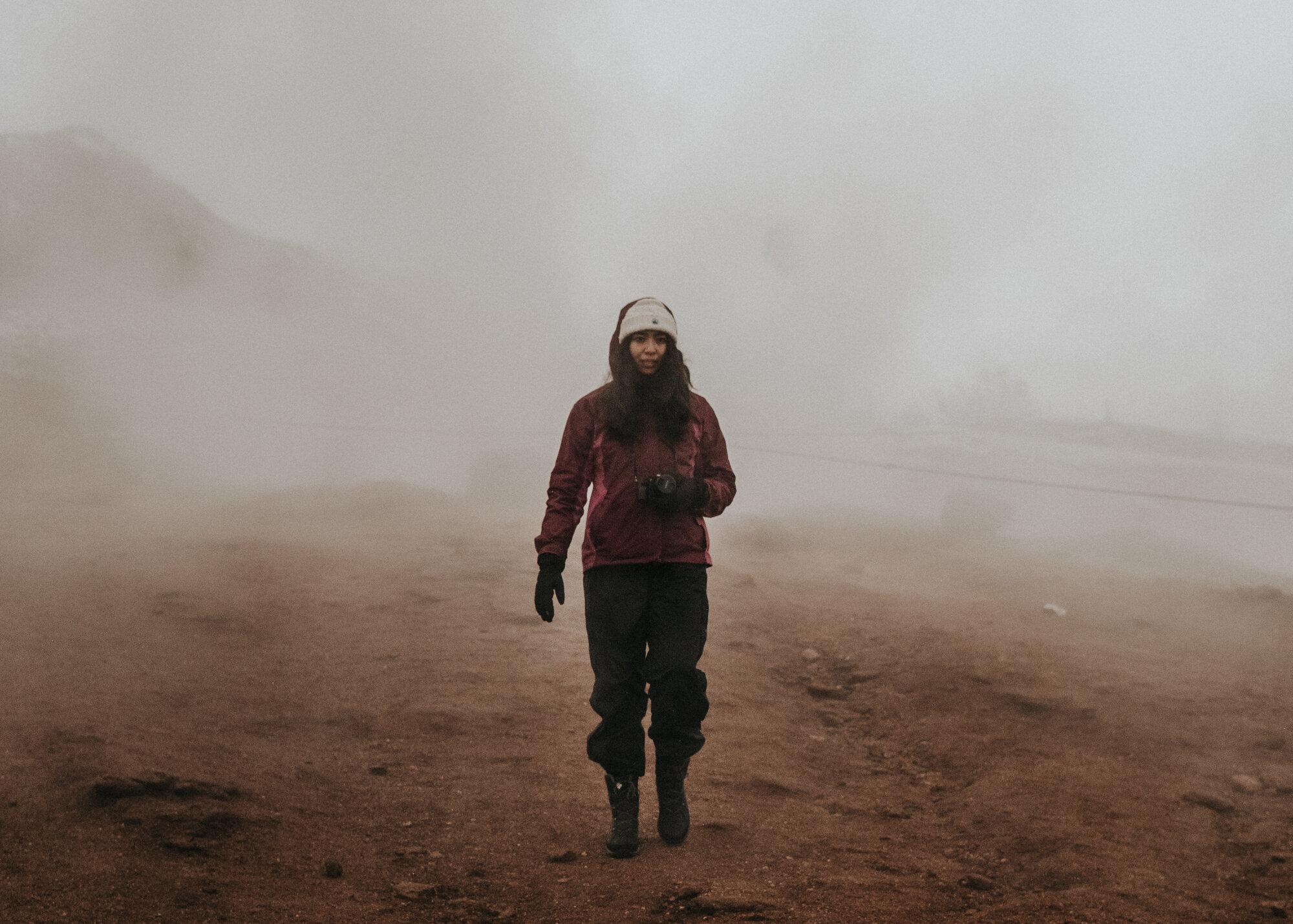 一个穿着冬装、带着相机和手套的女孩在一个地热站点的棕色土壤上走过朦胧的烟雾