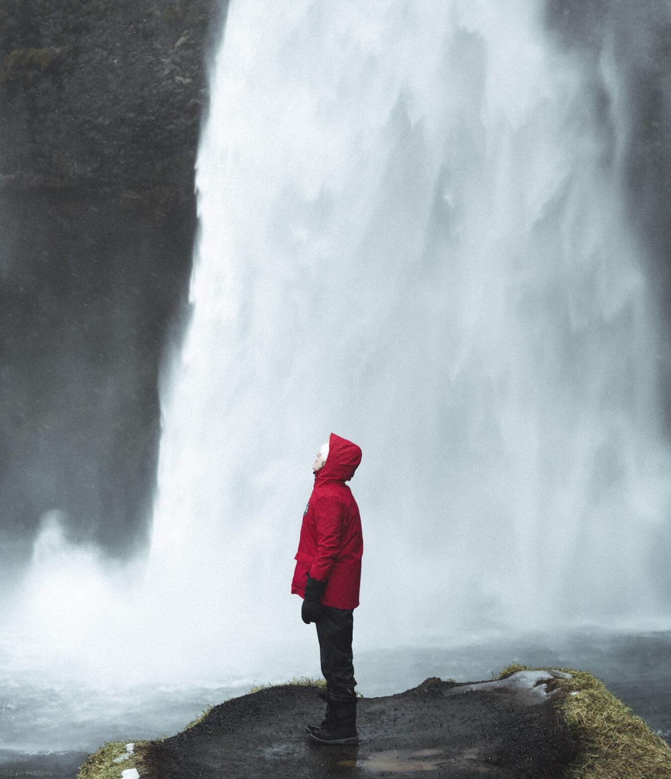 一个穿着红色外套和冬衣的人凝视着冰岛的Seljalandsfoss瀑布