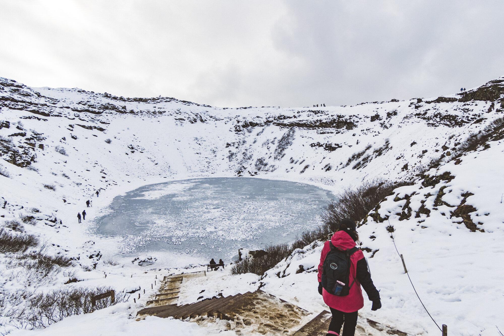 身穿红色大衣的人俯瞰着冰岛冰雪覆盖的火山口湖