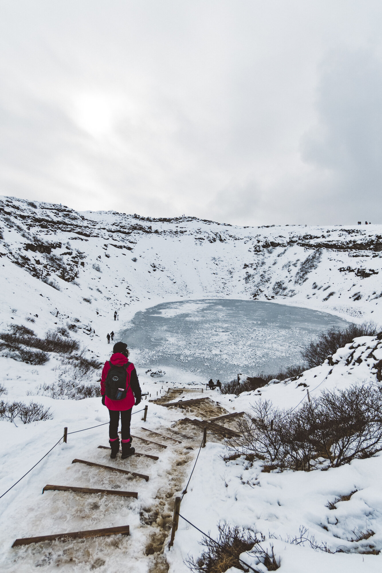 站立在冰冷的步的桃红色外套的人看雪和灌木围拢的一个冻蓝色火山口湖