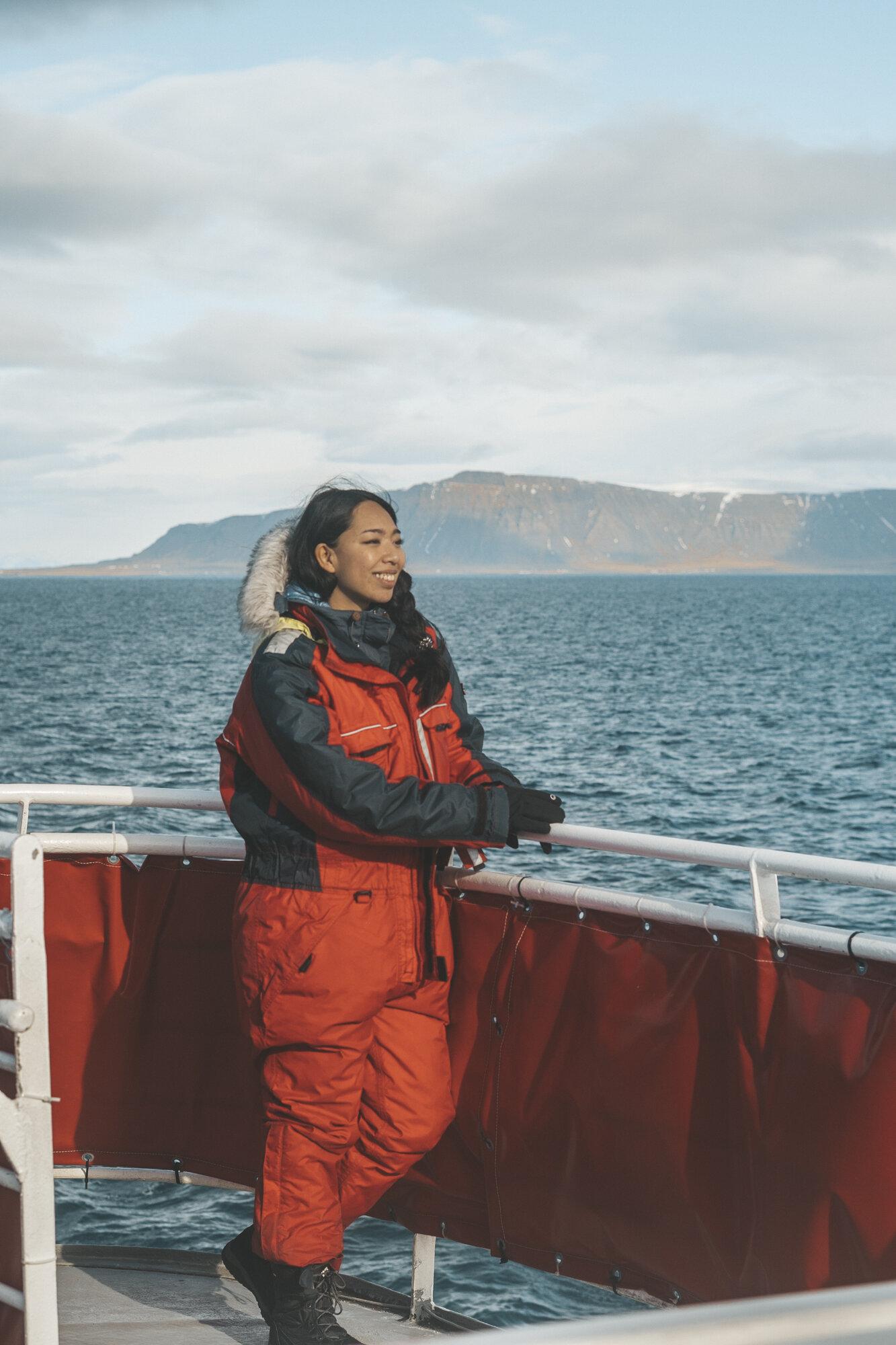 身穿红色工作服、头戴毛绒帽的女孩站在甲板上,背景是蓝色的大海和山脉