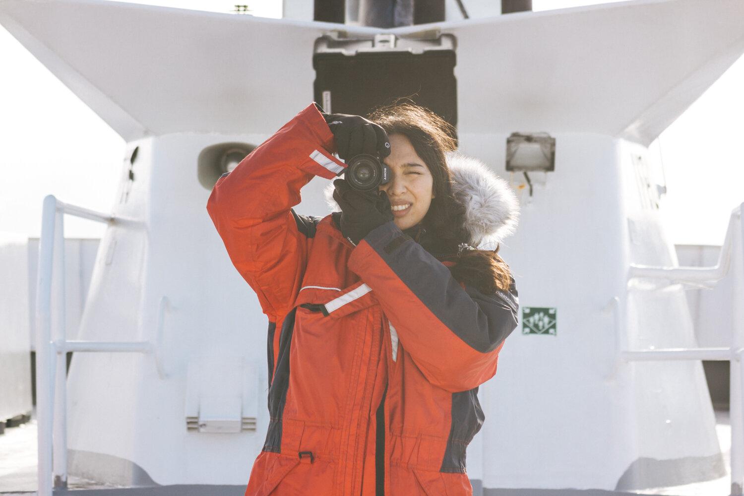 穿着红色工作服的女孩在冰岛的一艘船上用索尼A7iii相机拍摄照片