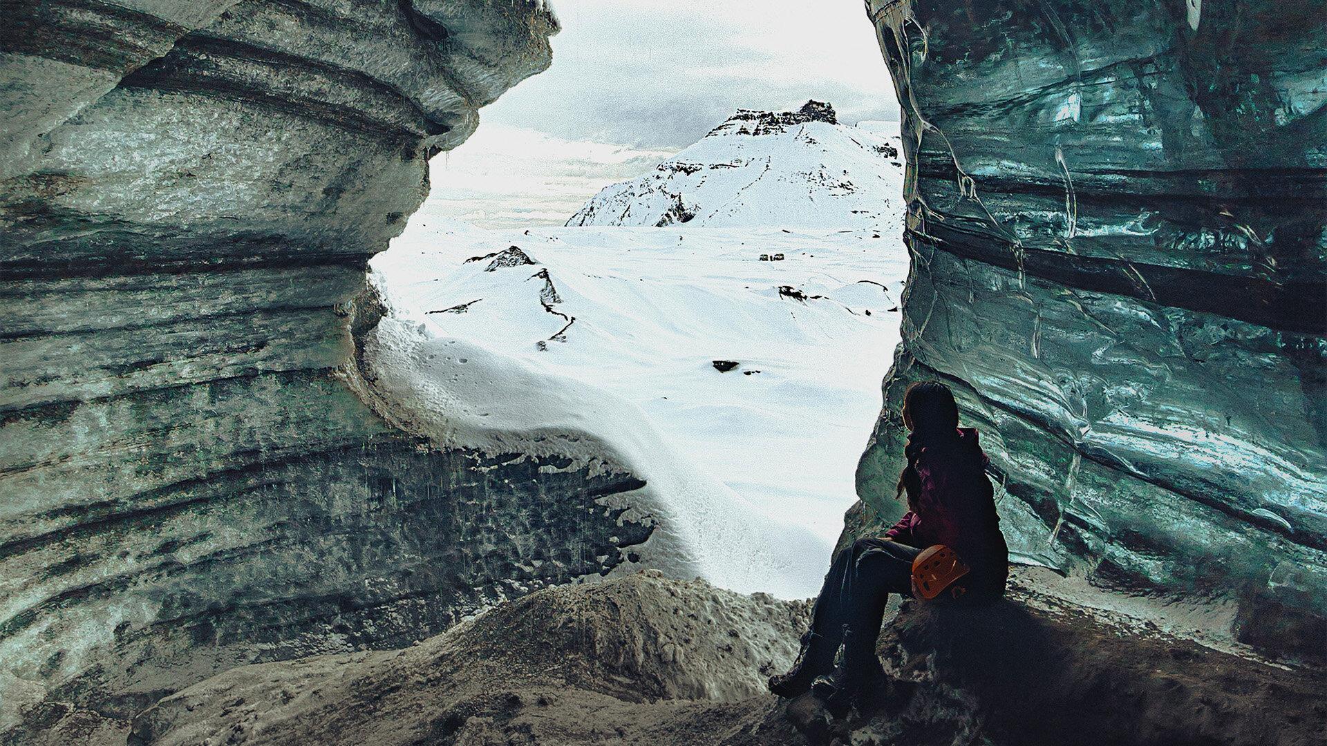 在冰岛的金圈,女孩坐在一个蓝色的冰洞里,凝视着远处白雪覆盖的山脉