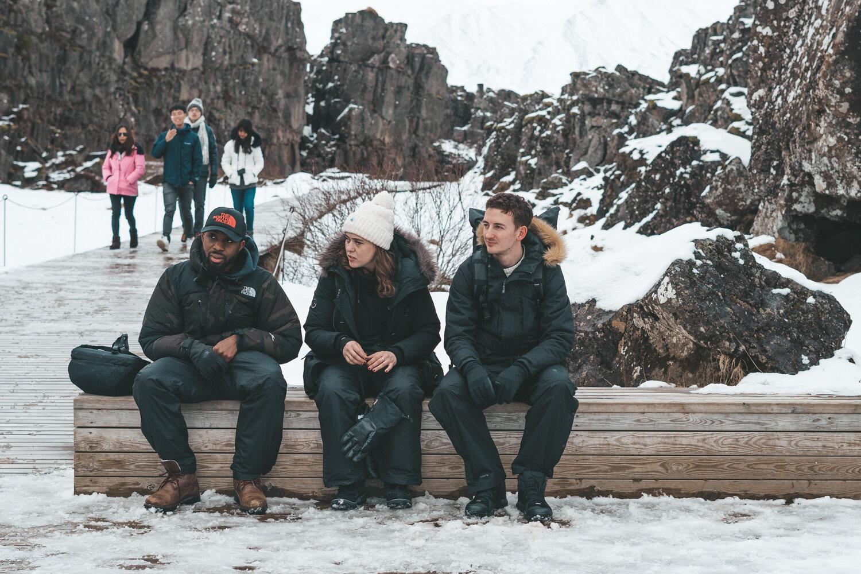 三个穿着冬衣的朋友坐在雪域公园的长凳上(冰岛,辛维利尔)