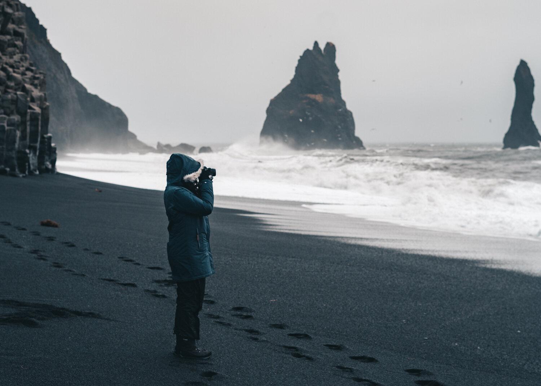 站立在一个黑沙子海滩的女孩与拍咆哮海的照相机的一个照相机