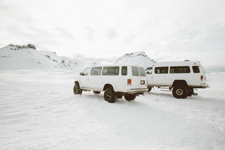 两辆白色雪地卡车停在冰岛雪白的山脉外