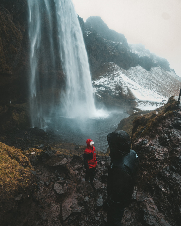两个人,一个穿黑衣服,一个穿红夹克,站在美丽的瀑布瀑布之间的岩石