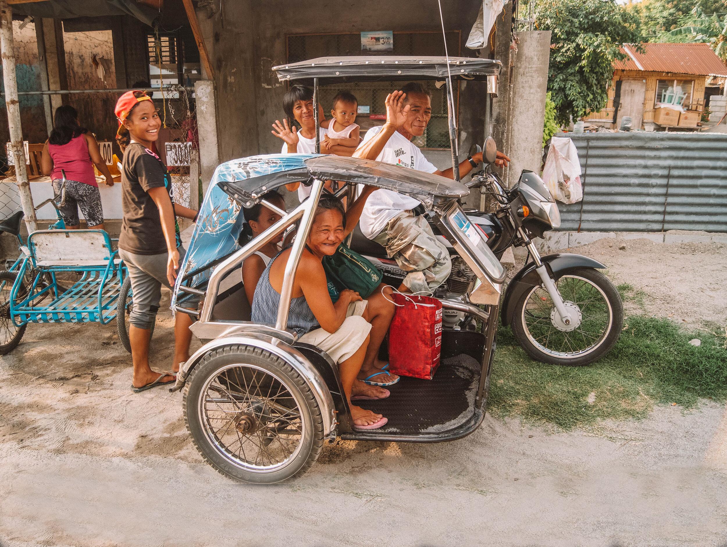 在Zambales,菲律宾当地人骑着三轮车对着镜头微笑