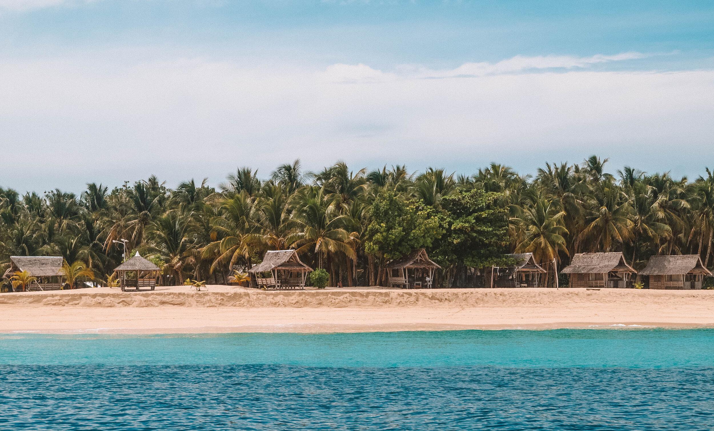 椰子树、碧绿的海水和白色的沙滩:菲律宾西阿尔高裸体岛的一片天堂