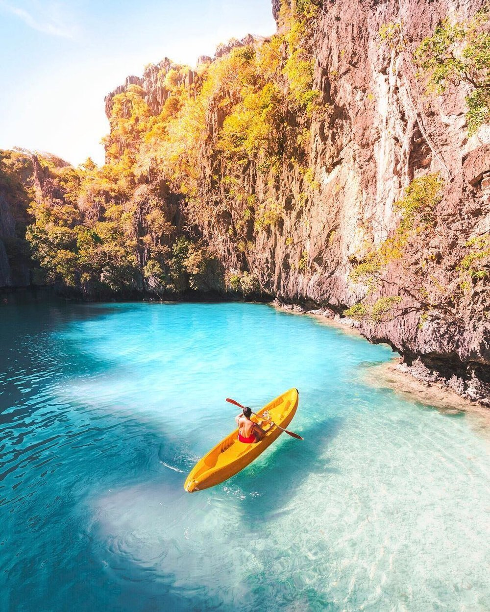 在菲律宾巴beplay3体育官方下载拉望岛的秘密泻湖里,梅尔在一艘黄色皮艇上划桨——摄影:乔丹·哈蒙德