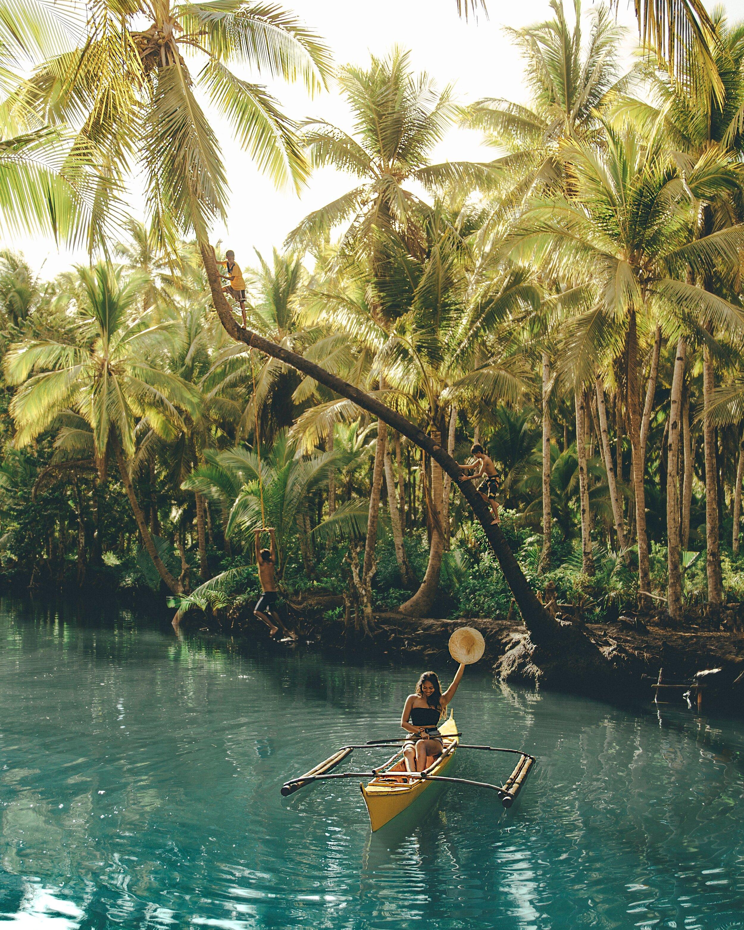 在菲律宾Siargao岛的一条河边,棕榈树成行——我坐在黄色的独木舟上,当地的孩子在我身后爬树!