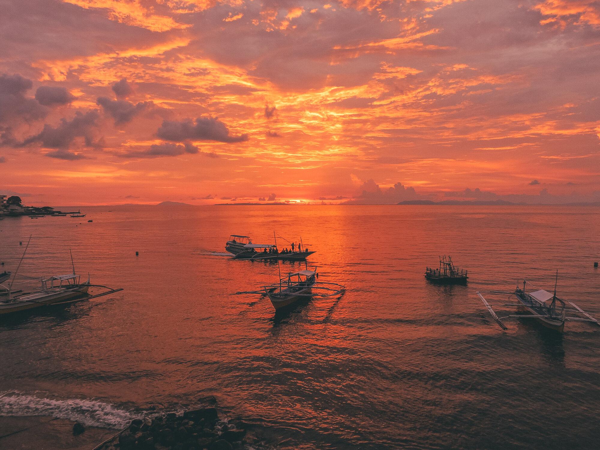 菲律宾八打加斯-吕宋岛,马比尼,阿尼劳,海上火红的日落和漂浮的船只