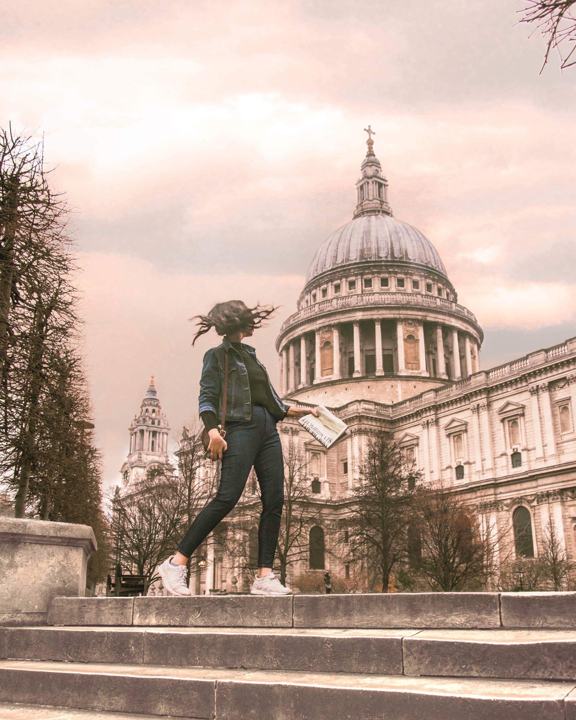 穿着牛仔装,手拿报纸走在伦敦圣保罗大教堂外