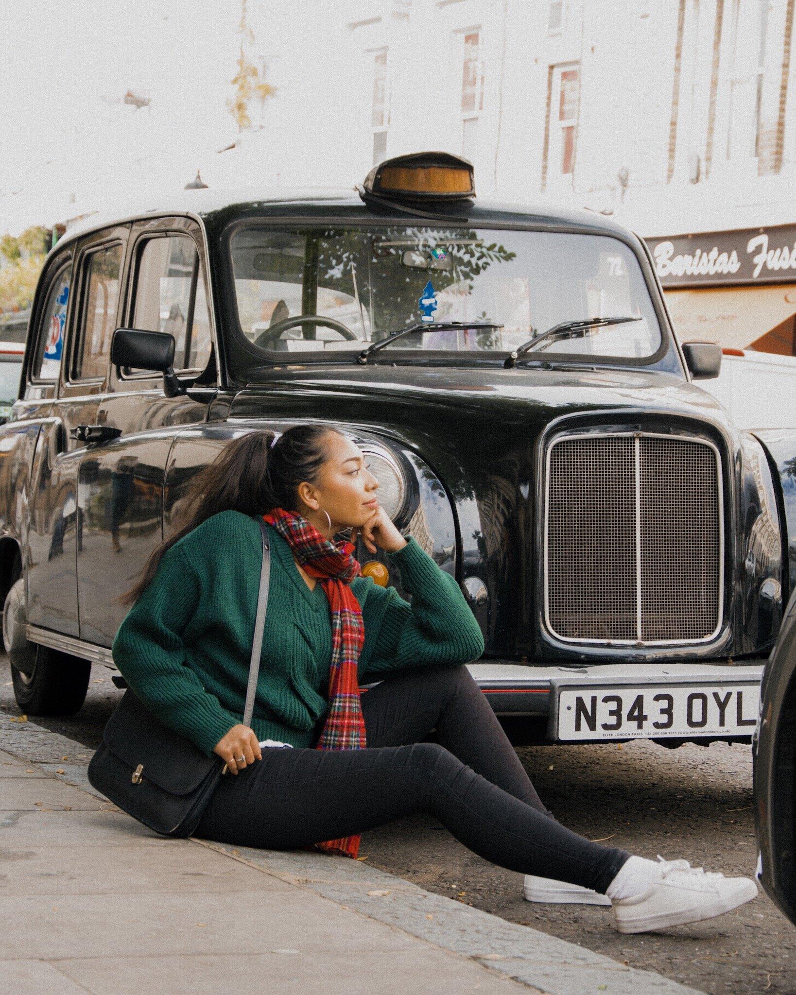 坐在波多贝罗的人行道上,一辆标志性的传统伦敦黑色出租车前,身穿绿色针织套头衫,戴着红色格子围巾