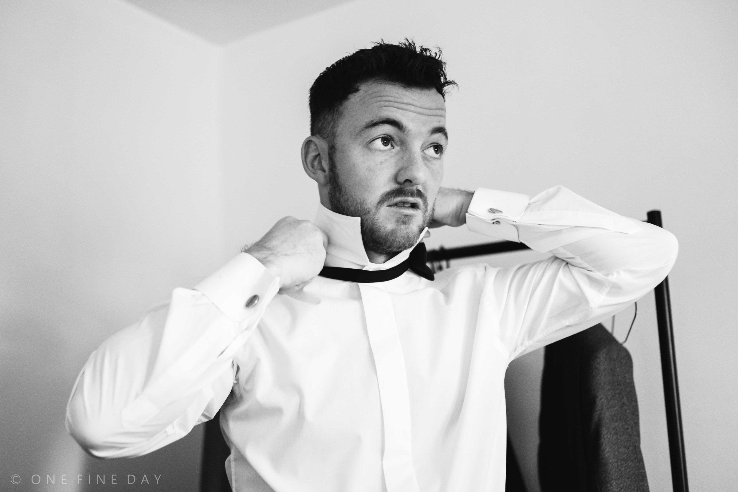 Black and white image of the groom on his wedding day