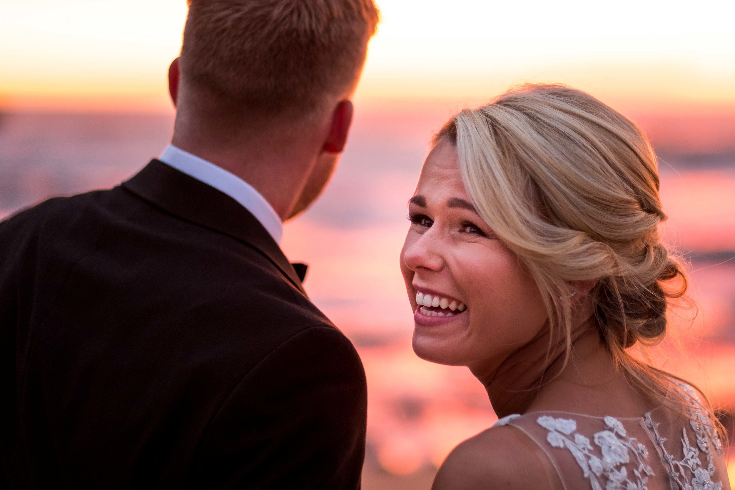 Natural and un-posed photograph of Bride laughing on the beach at Sunset on her wedding day