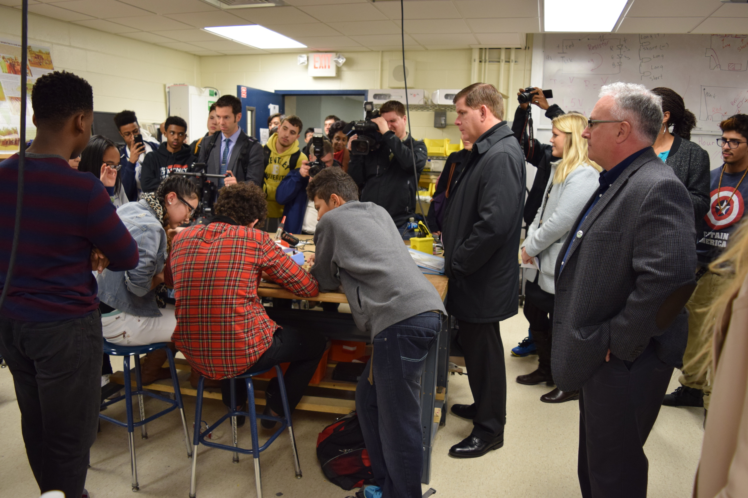 Engineering students show off the Christmas ornaments they are sautering to Mayor Walsh in the workshop the MIT Edgarton Center helped make a reality.