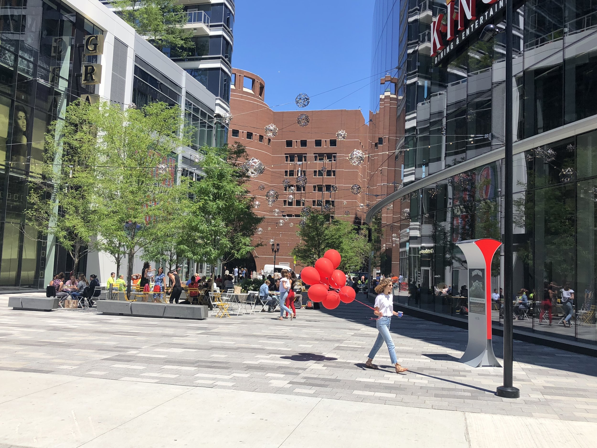 A woman strolls past the Soofa Sign in Seaport One with some balloons.